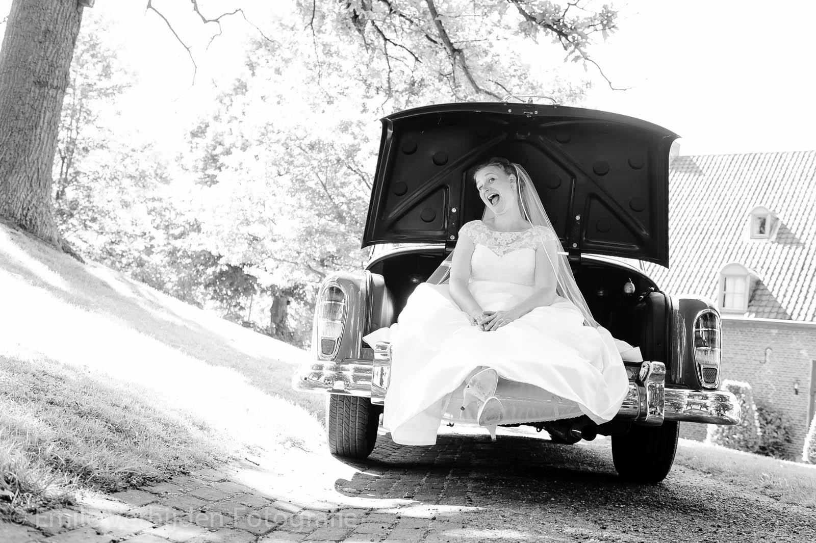 Bruidje in de kofferbak van de bruidsauto bij Winselerhof te Landgraaf. Bruidsfotograaf Kerkrade Emile Verhijden