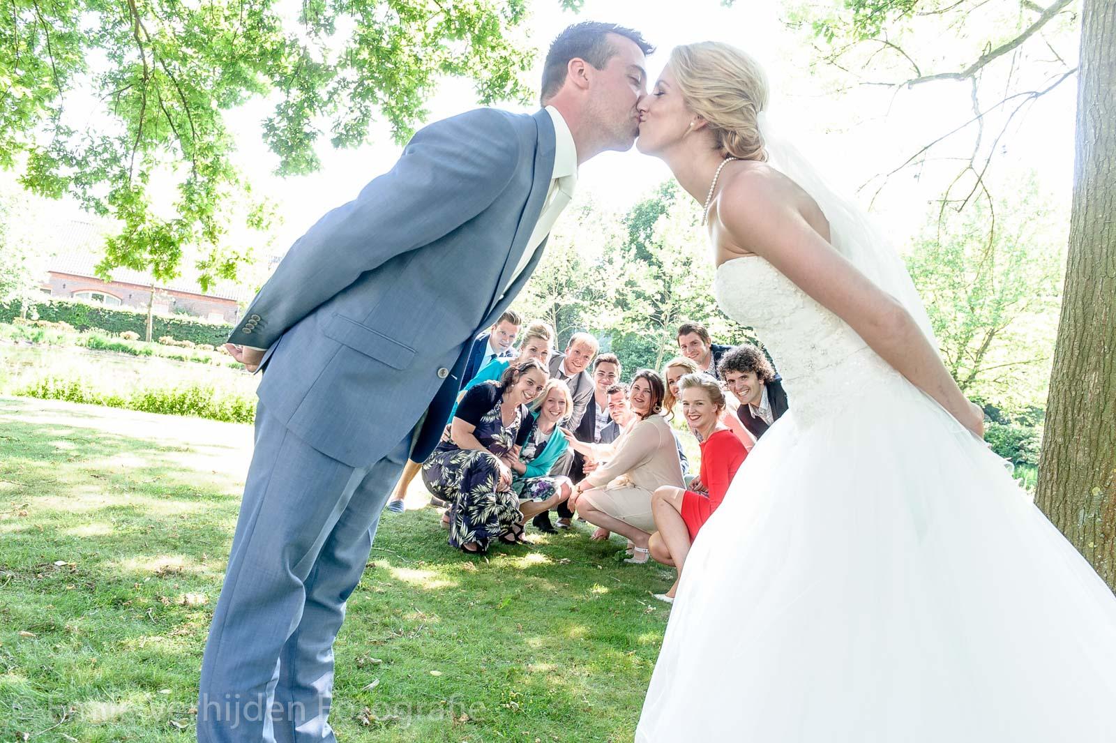 Bruidspaar kust terwijl alle vrienden toekijken bij Chateau de Raay in Baarlo bruidsfotograaf Limburg Emile Verhijden