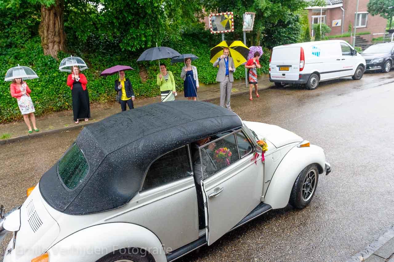 De bruidegom komt de bruid ophalen. Uitstappen uit de bruidsauto in stromende regen. Bruidsfotograaf Roermond trouwreportage John en Desiree