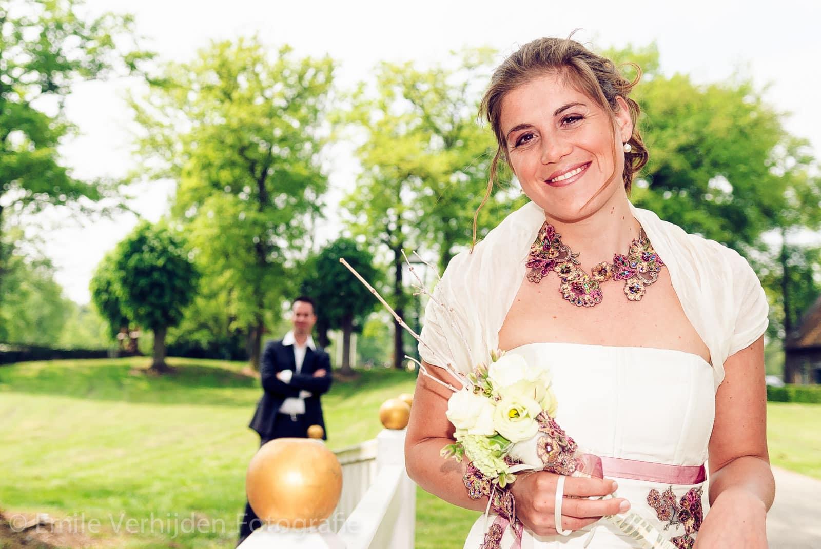 Bruidsfotograaf Limburg - scherpte diepte foto met stralende bruid op voorgrond.