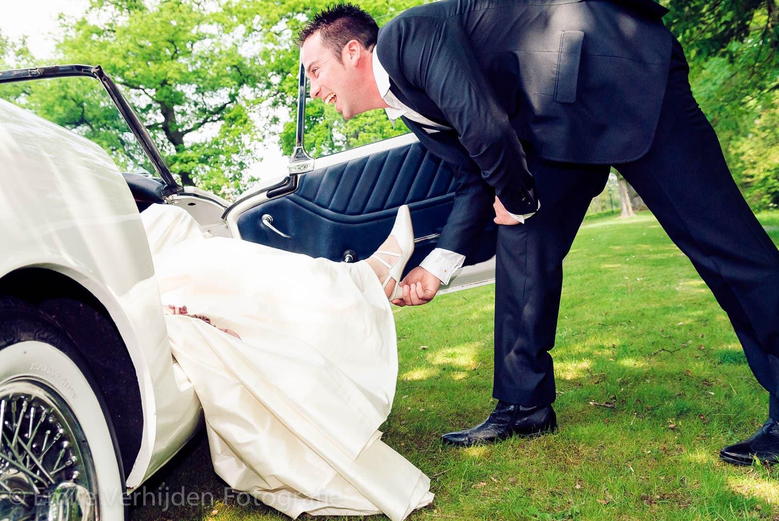 Bruidsfotograaf Limburg - De bruidegom gaat de voeten van de bruid kussen. Ze zit lekker in de oldtimer