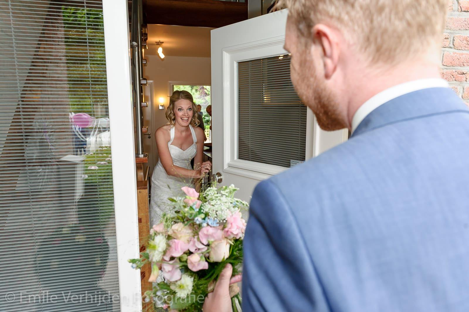Bruid doet de deur open voor de bruidegom