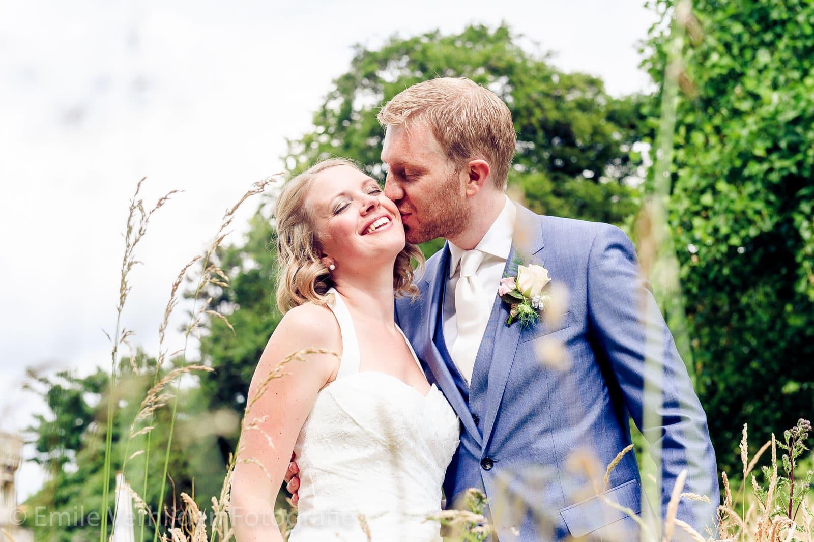 Stralende bruid tussen het gras, door bruidsfotograaf Limburg Emile Verhijden
