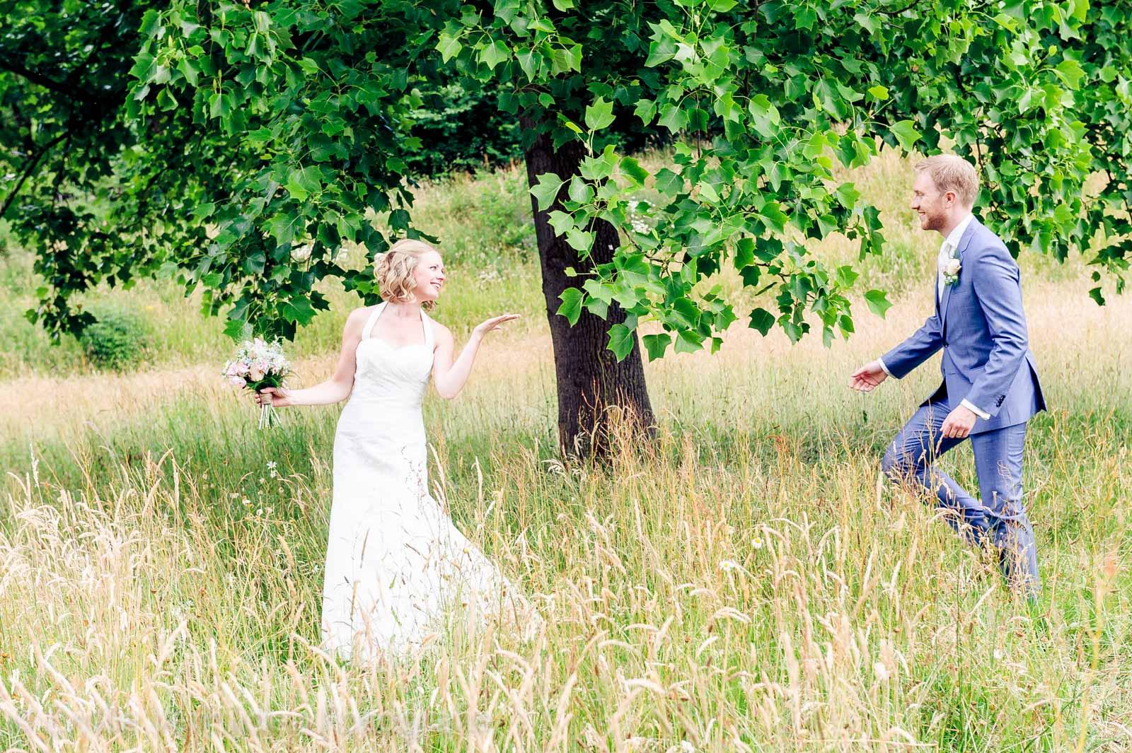 Bruidegom loopt door het gras naar de bruid trouwfotograaf Kasteel Elsloo