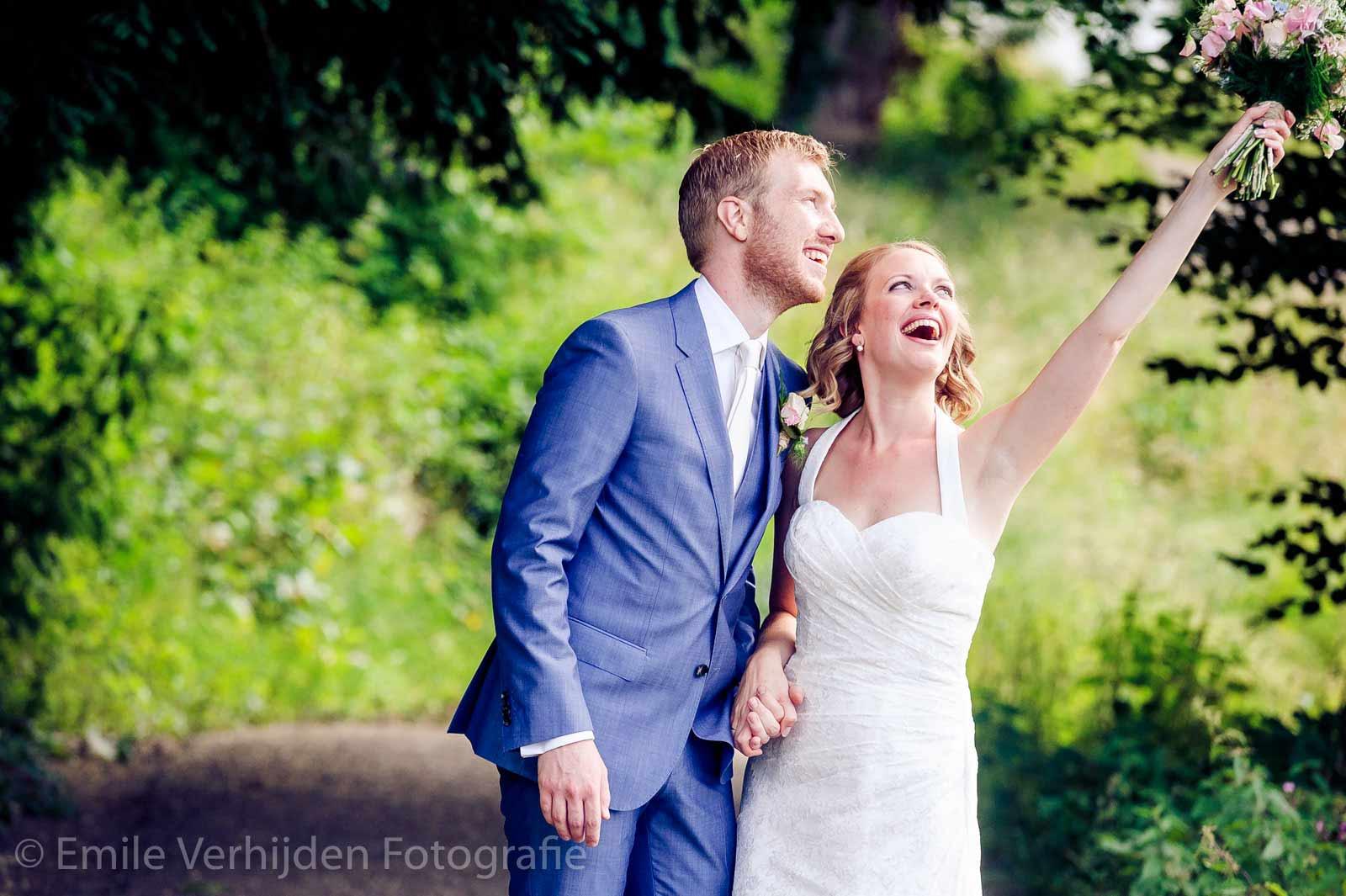 Een gelukkige bruid gooit boeket omhoog bij Kasteel Elsloo op de berg. Bruidsfotograaf Elsloo Emile Verhijden