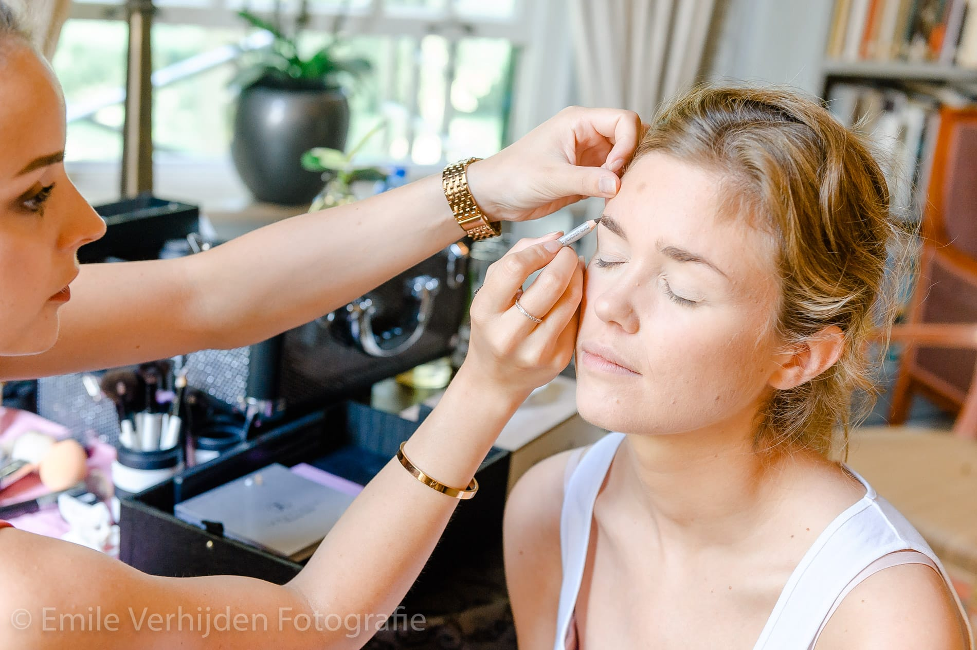 De make-up wordt aangebracht. Bruidsfotograaf Limburg Emile Verhijden