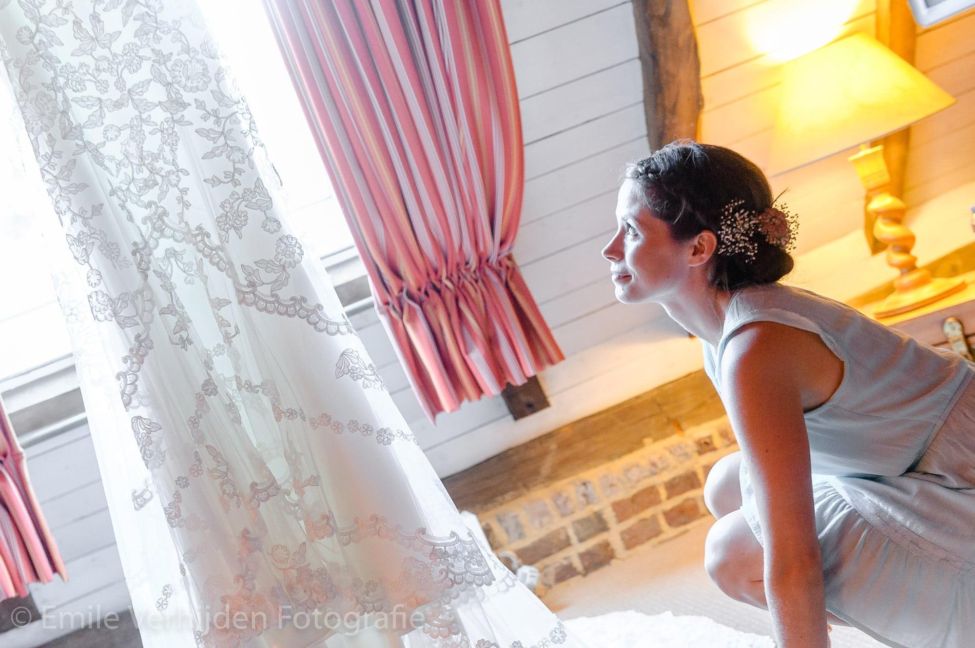 De bruid kijkt naar de jurk bij Winselerhof Landgraaf. Bruidsfotografie Winselerhof Landgraaf - Kerkrade