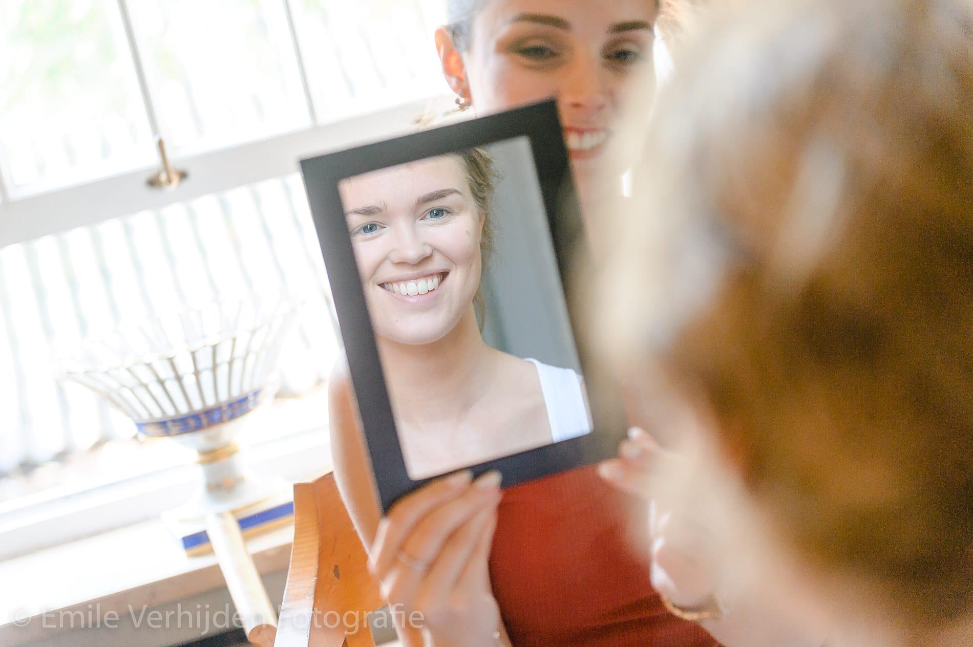 Bruid kijkt in spiegel. Bruidsfotograaf Limburg Emile Verhijden