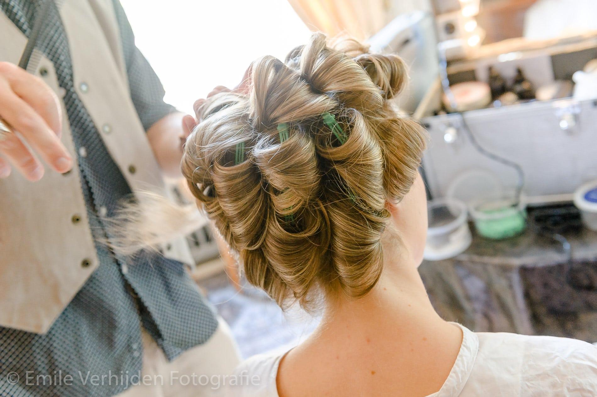 De haren van de bruid zitten helemaal in de krulspelden. Bruidsfotograaf Grathem Limburg Emile Verhijden