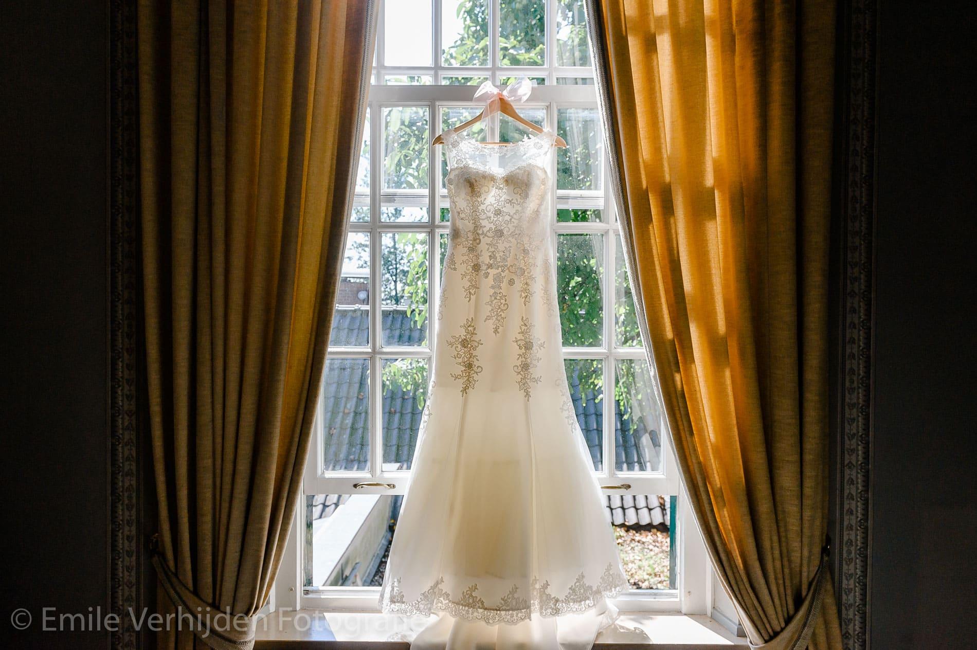 De prachtige jurk van de bruid hangt aan het raam. Bruidsfotograaf Kasteel Groot Buggenum Grathem Limburg Emile Verhijden