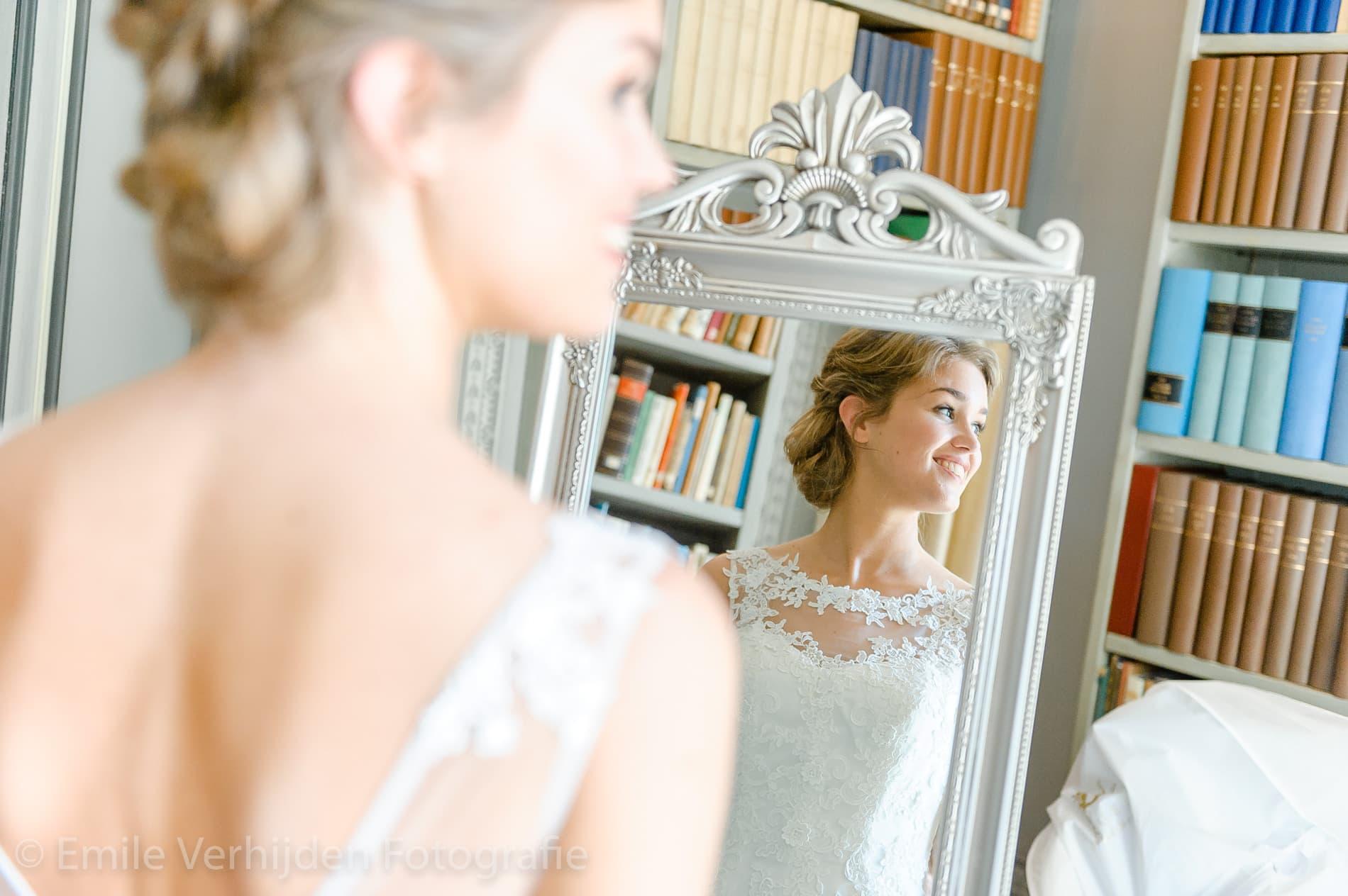 Bruid kijkt in spiegel. Trouwfotograaf Limburg Emile Verhijden