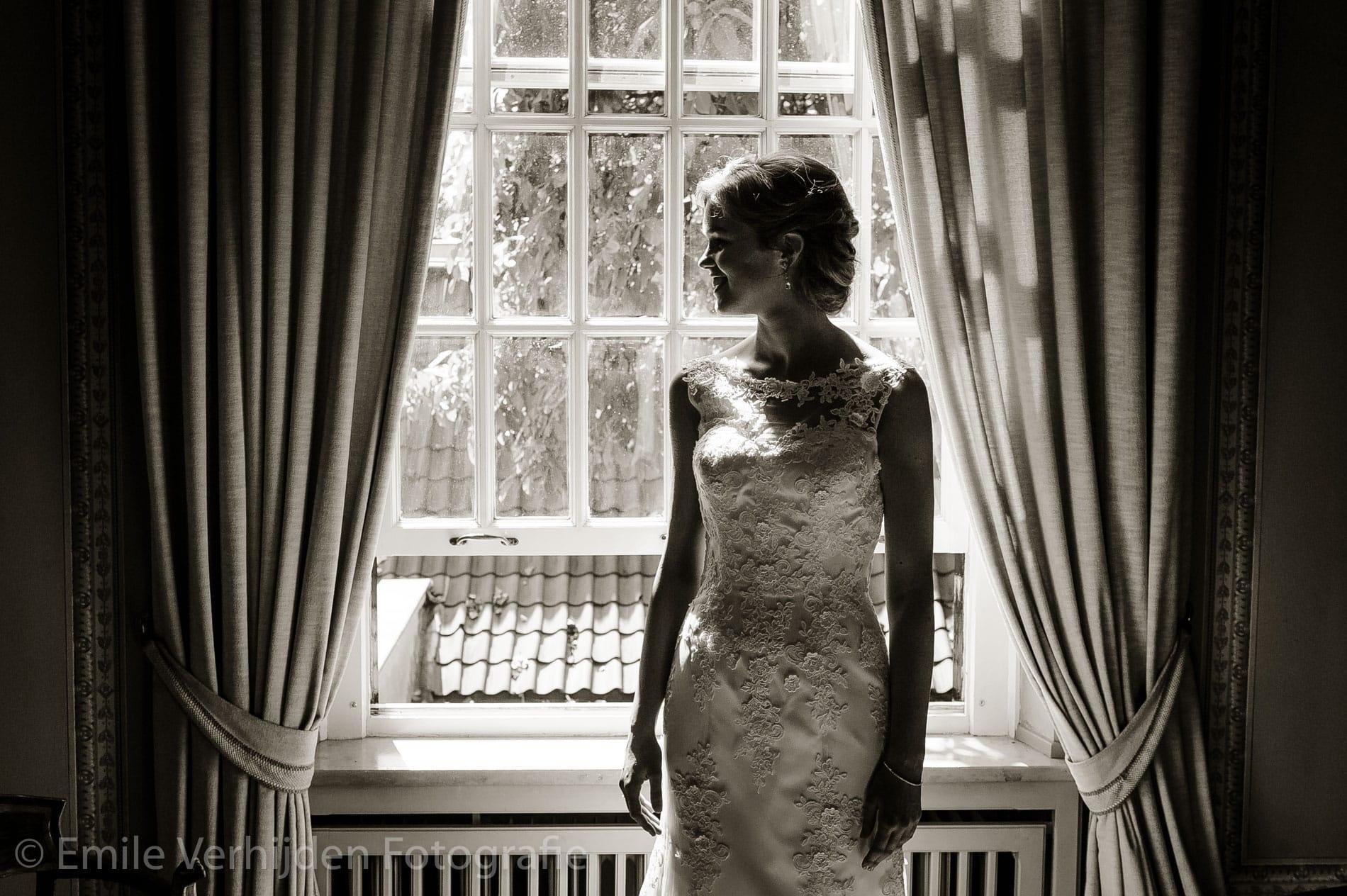 Mooie zwart-wit tegenlicht opname van de bruid. Bruidsfotograaf Limburg Emile Verhijden