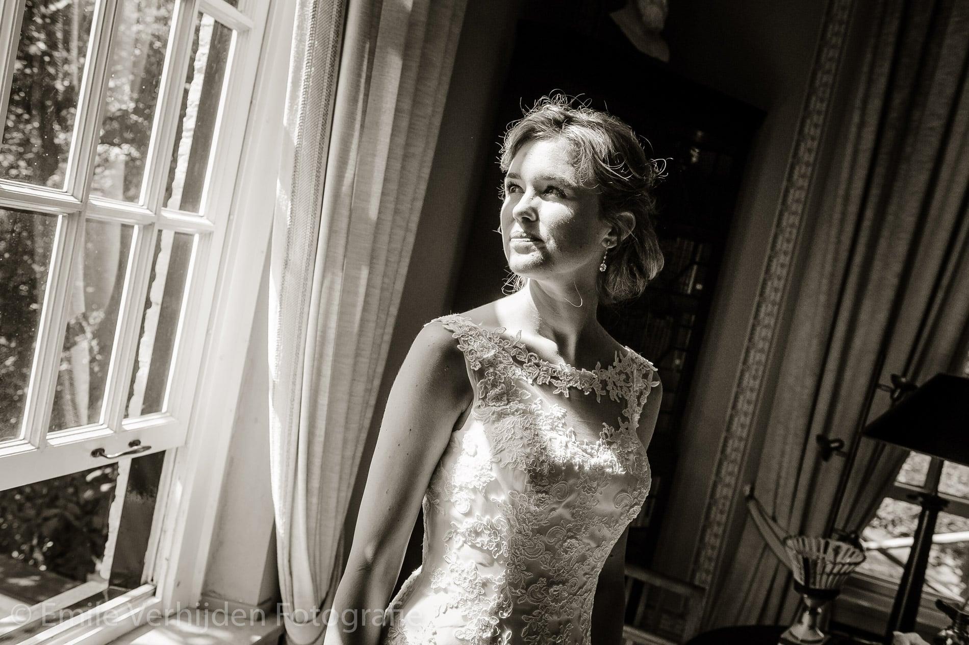 Bruid kijkt naar buiten. Trouwfotograaf Limburg Emile Verhijden