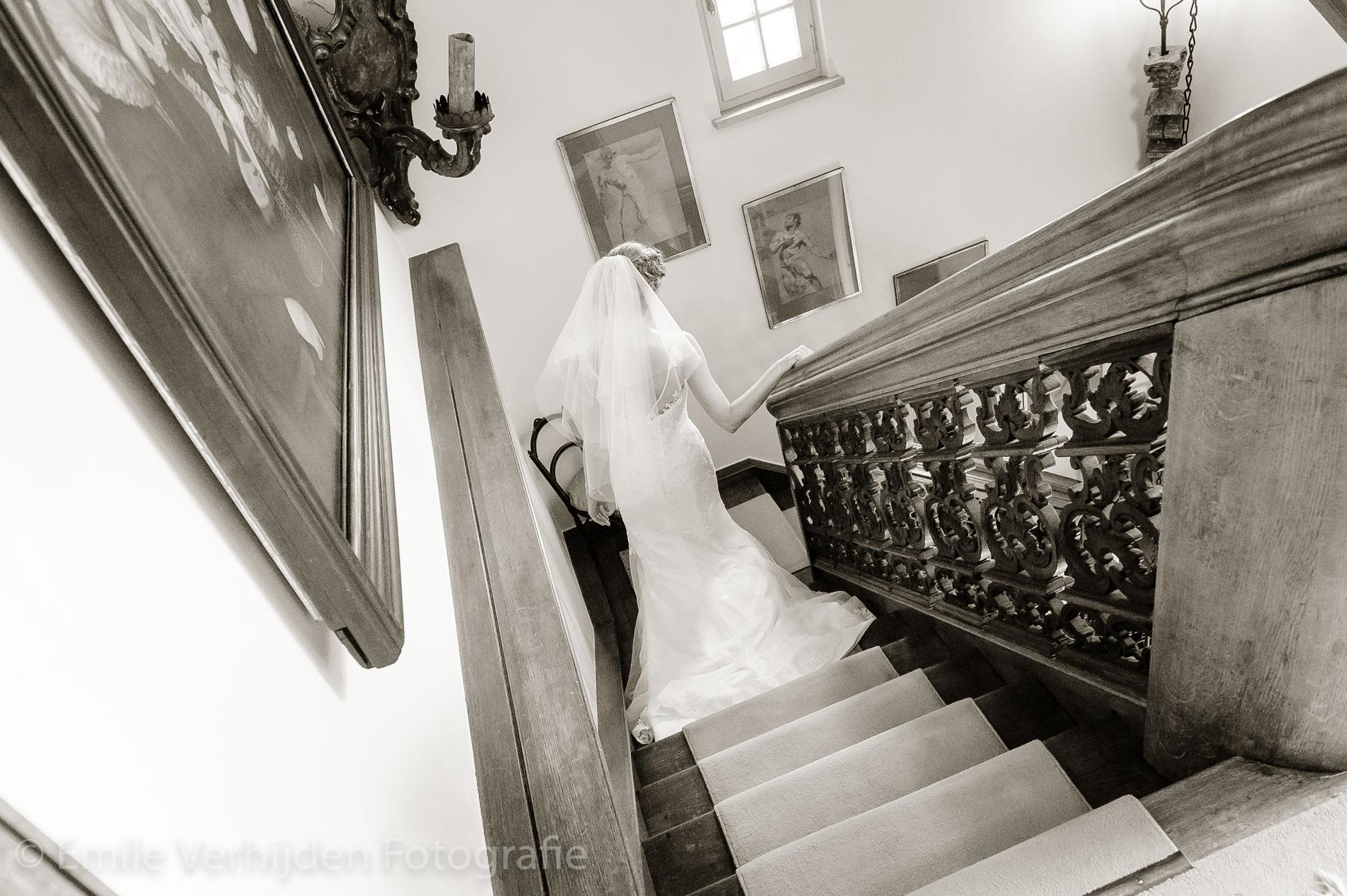 Voorzichtig loopt de bruid van de trap af. Bruidsfotograaf Grathem Limburg Emile Verhijden