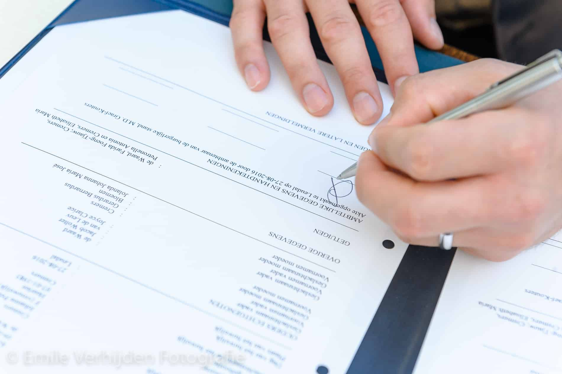 De handtekening onder de akte wordt gezet. Trouwfotograaf Limburg Emile Verhijden