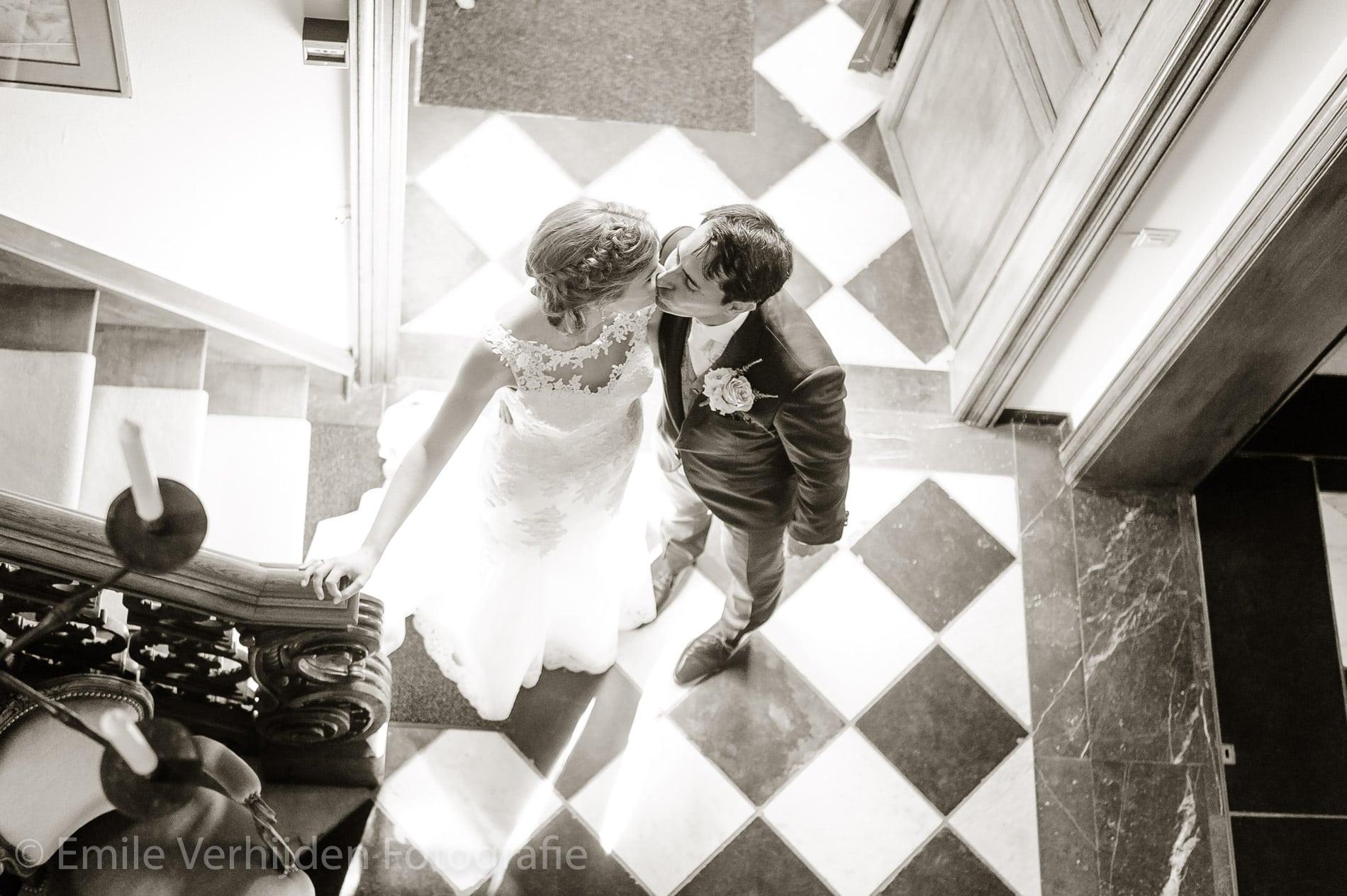 Een kus onder aan de trap. Bruidsfotograaf Kasteel Groot Buggenum Grathem Limburg