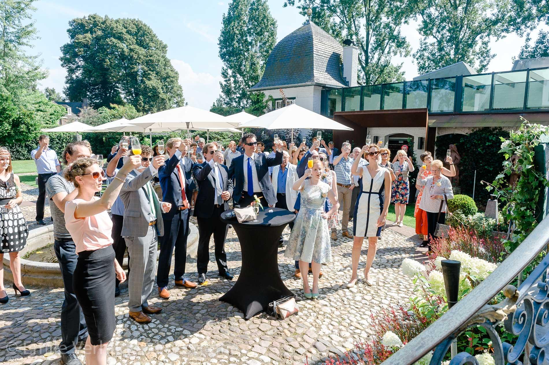 De toast wordt uitgebracht met vrienden en familie. Bruidsfotograaf Kasteel Groot Buggenum Grathem Limburg