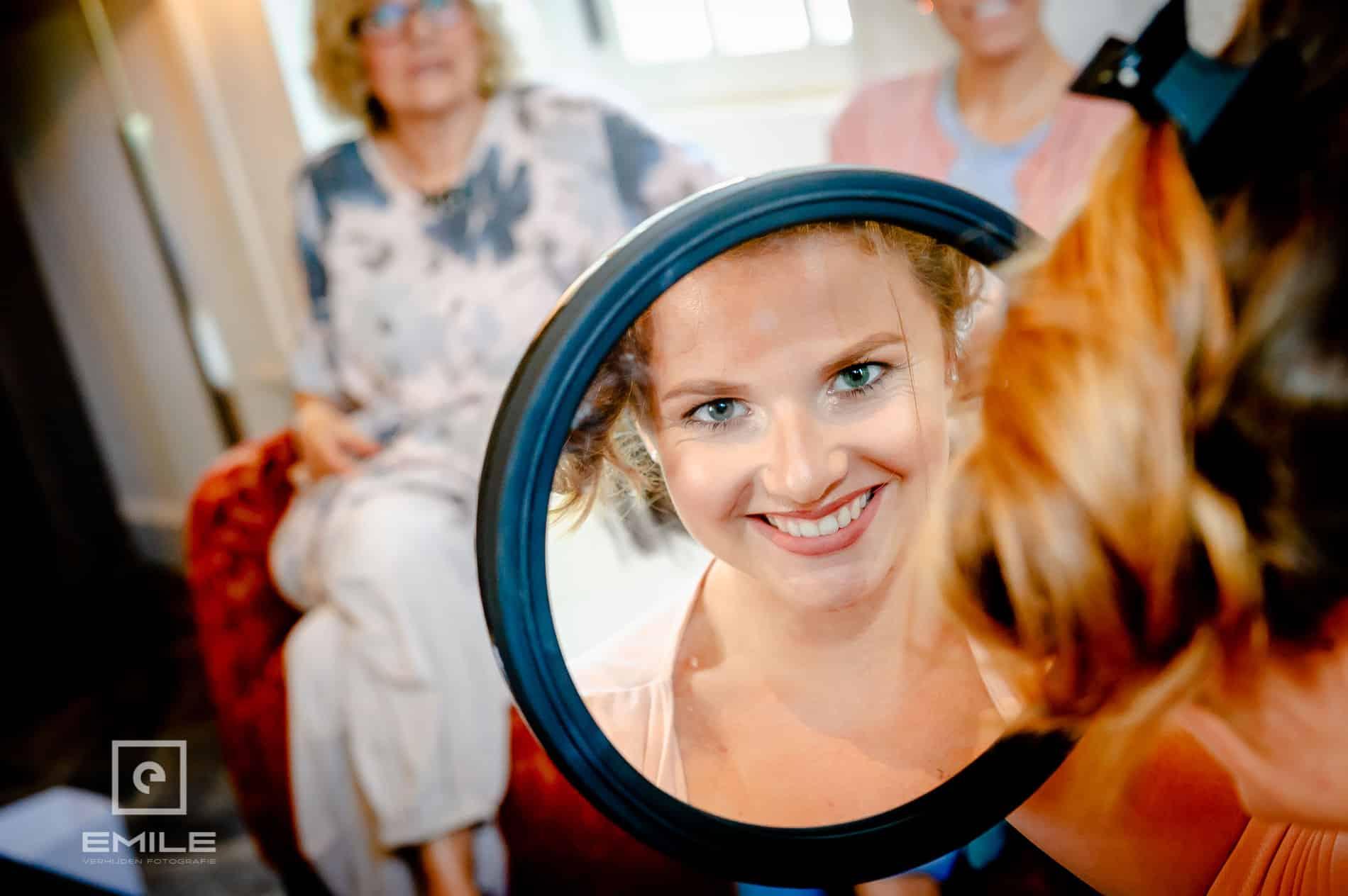 Bruid kijkt in spiegel. Bruidsfotograaf Limburg - Kasteel Daelenbroeck - Herkenbosch