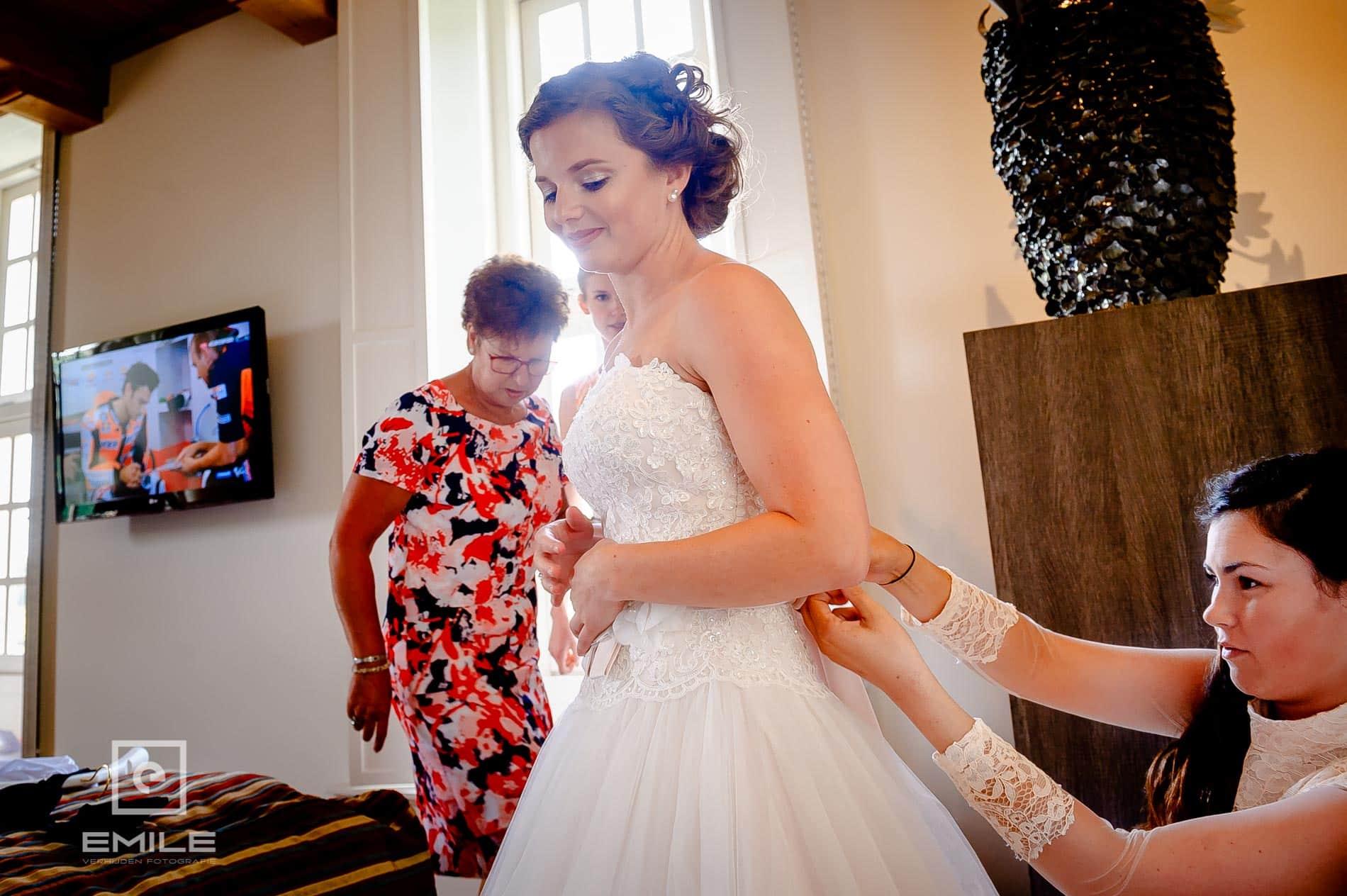 De jurk wordt aangetrokken. Bruidsfotograaf Limburg - Kasteel Daelenbroeck - Herkenbosch