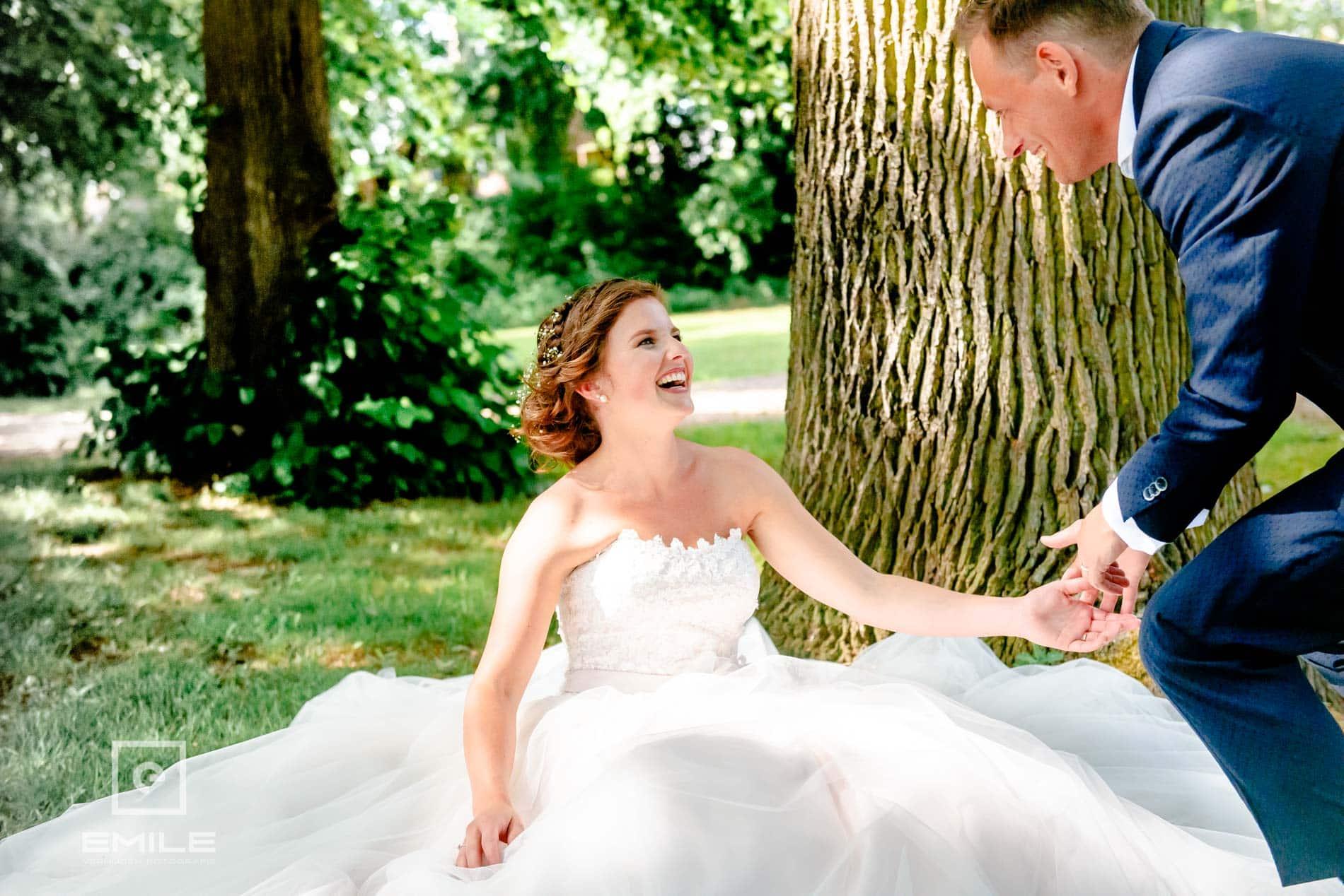 lachende bruid op de grond bij Kasteel Daelenbroeck - Herkenbosch