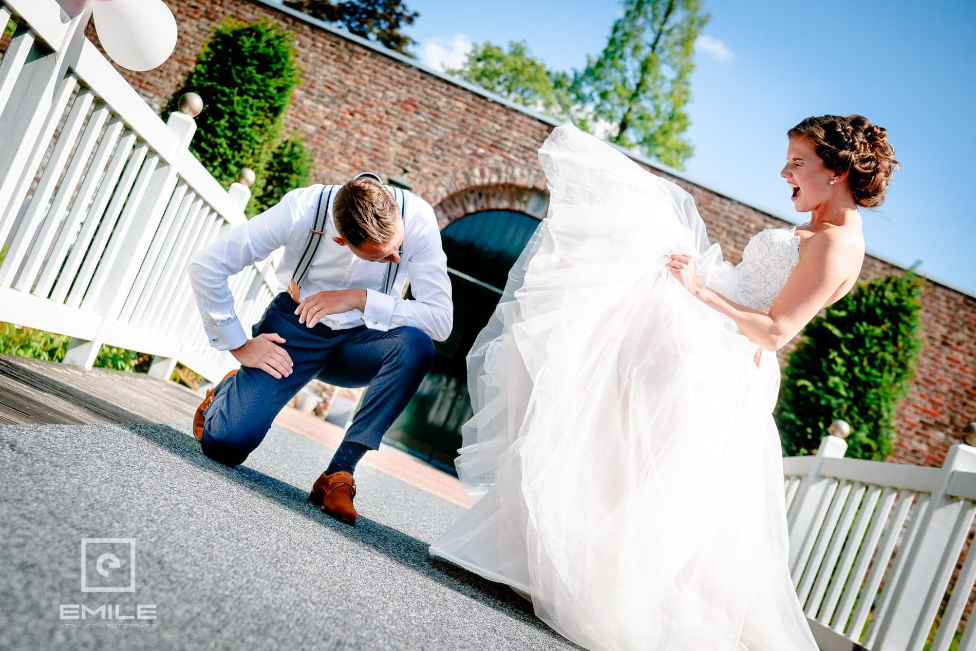 Bruidegom kijkt onder de rok van de bruid. Bruidsfotograaf Limburg - Kasteel Daelenbroeck - Herkenbosch