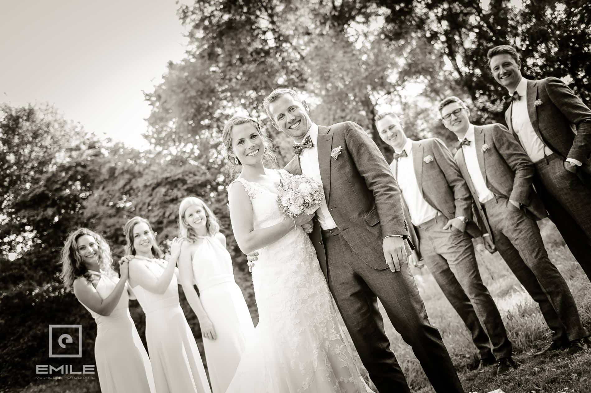 Bruidsfotograaf Landgraaf - Winselerhof. Bruidspaar kijkt naar fotograaf, vrienden staan onscherp in de achtergrond