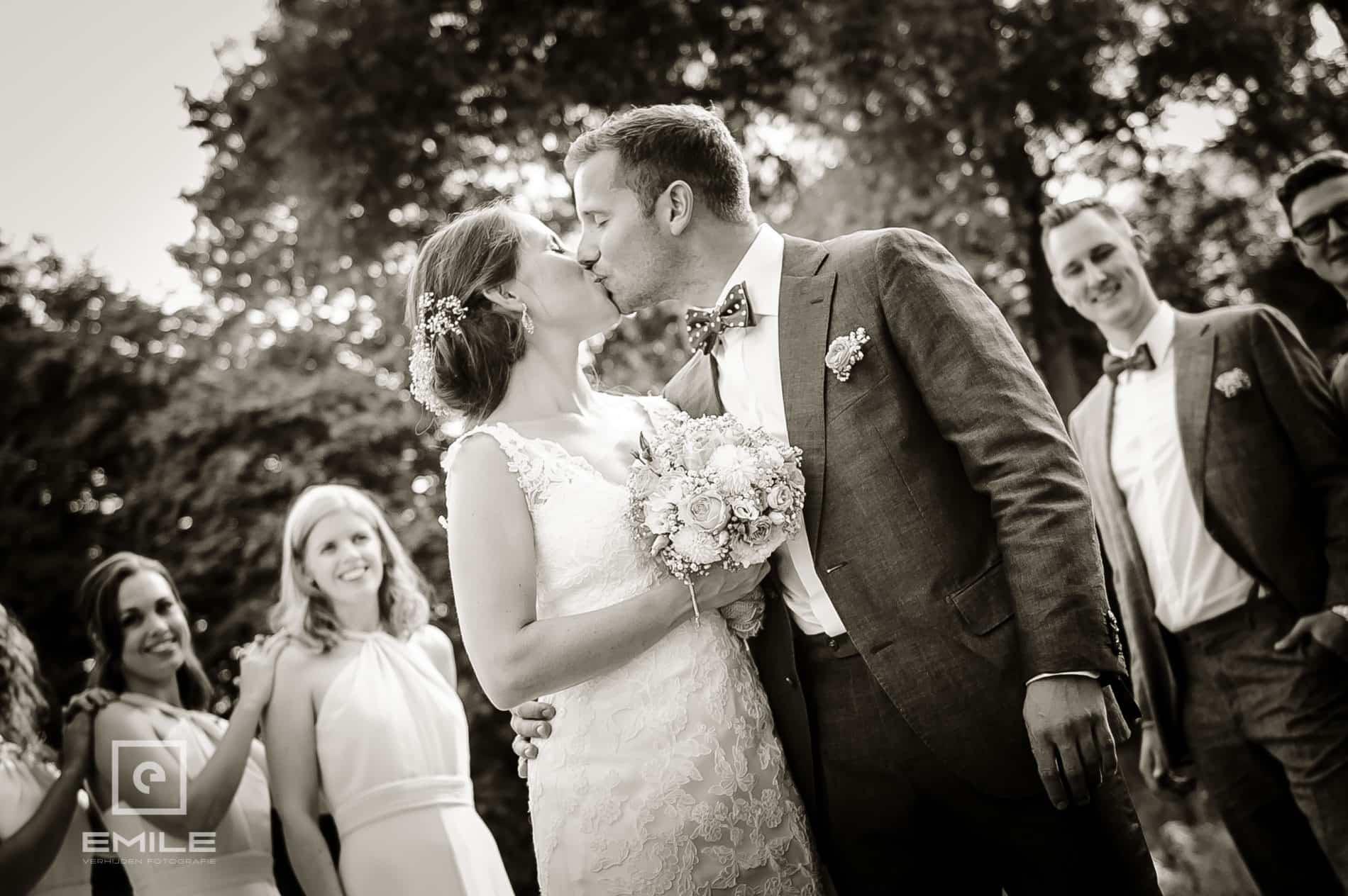 Bruidsfotograaf Landgraaf - Winselerhof. Bruidspaar kust, vrienden staan onscherp in de achtergrond