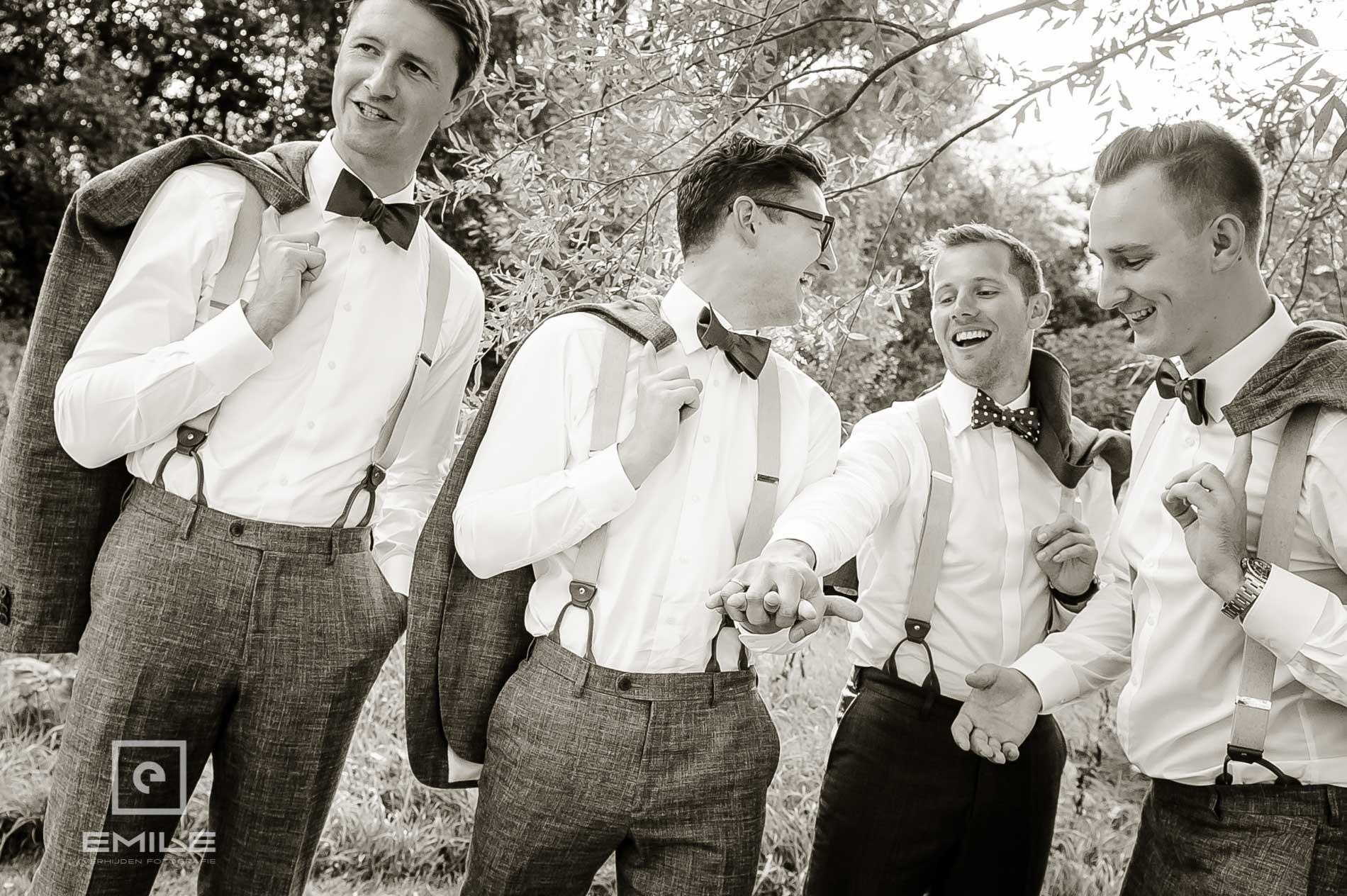 De mannen zijn samen met de bruidegom gek aan het doen met hun handen