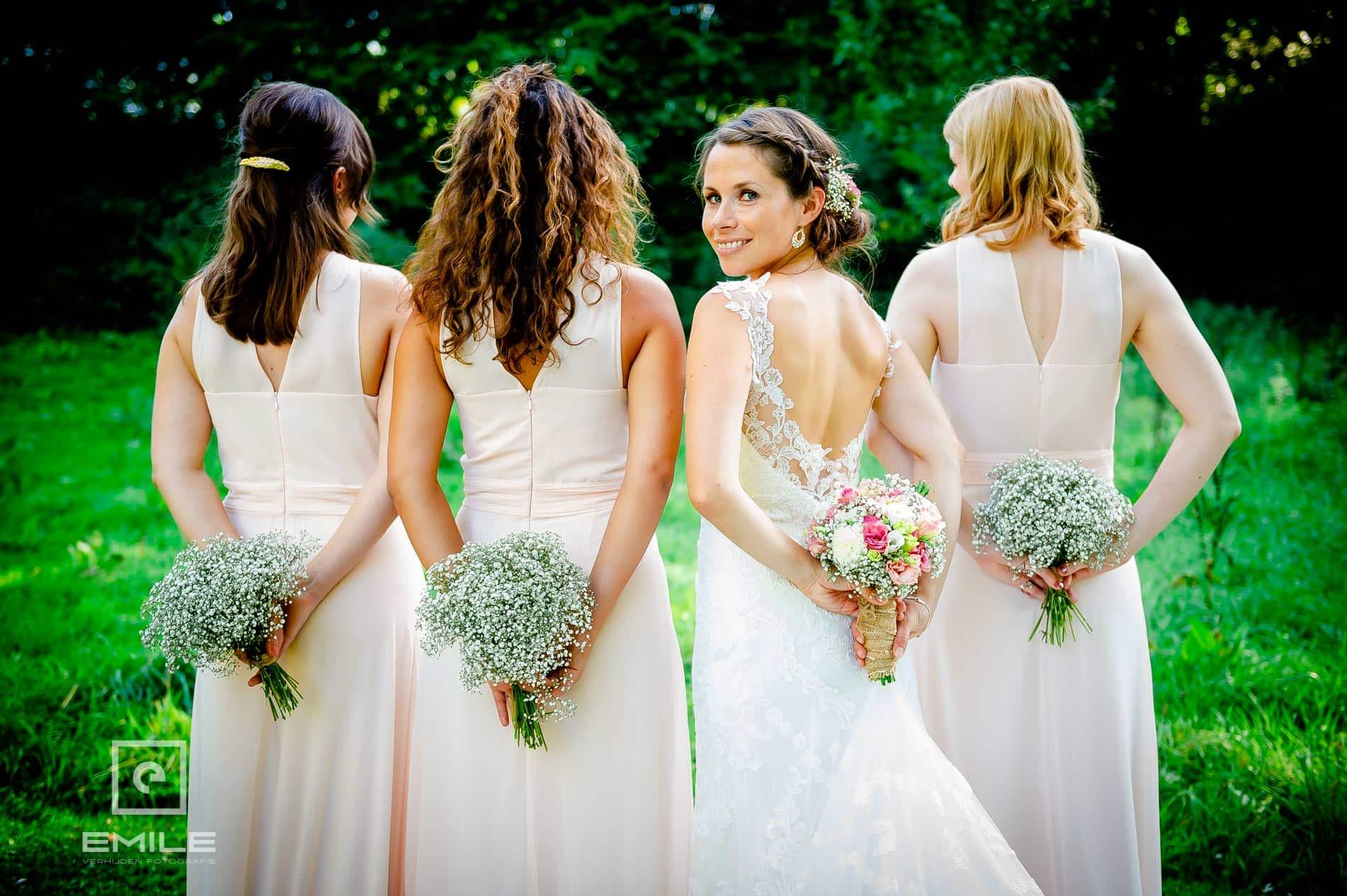 Bruidsmeisjes met boeket op rug, bruid kijkt achterom