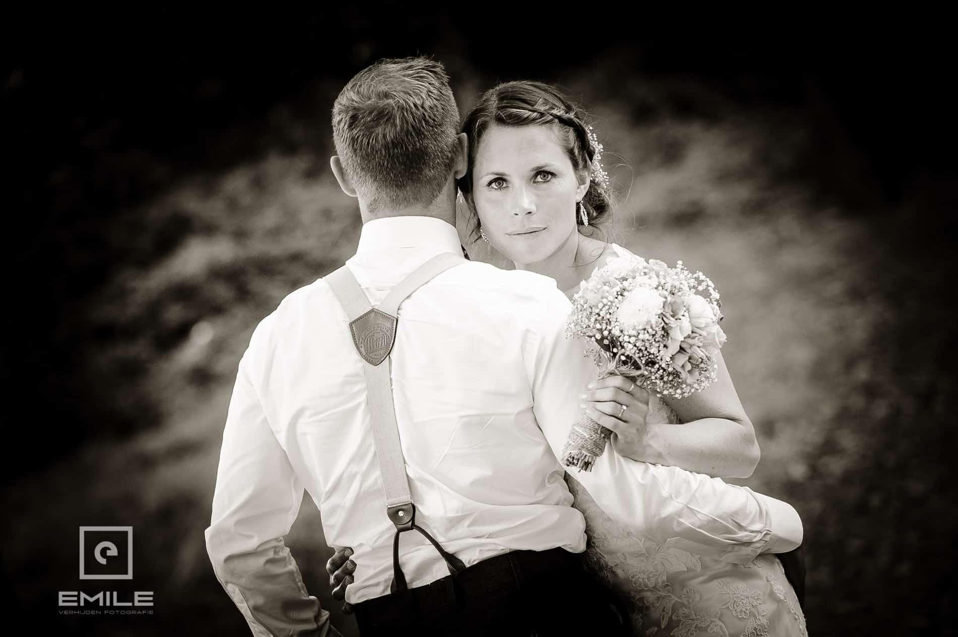 Bruid kijkt naar camera, bruidegom kijkt vooruit. Bruidsfotograaf Landgraaf - Winselerhof
