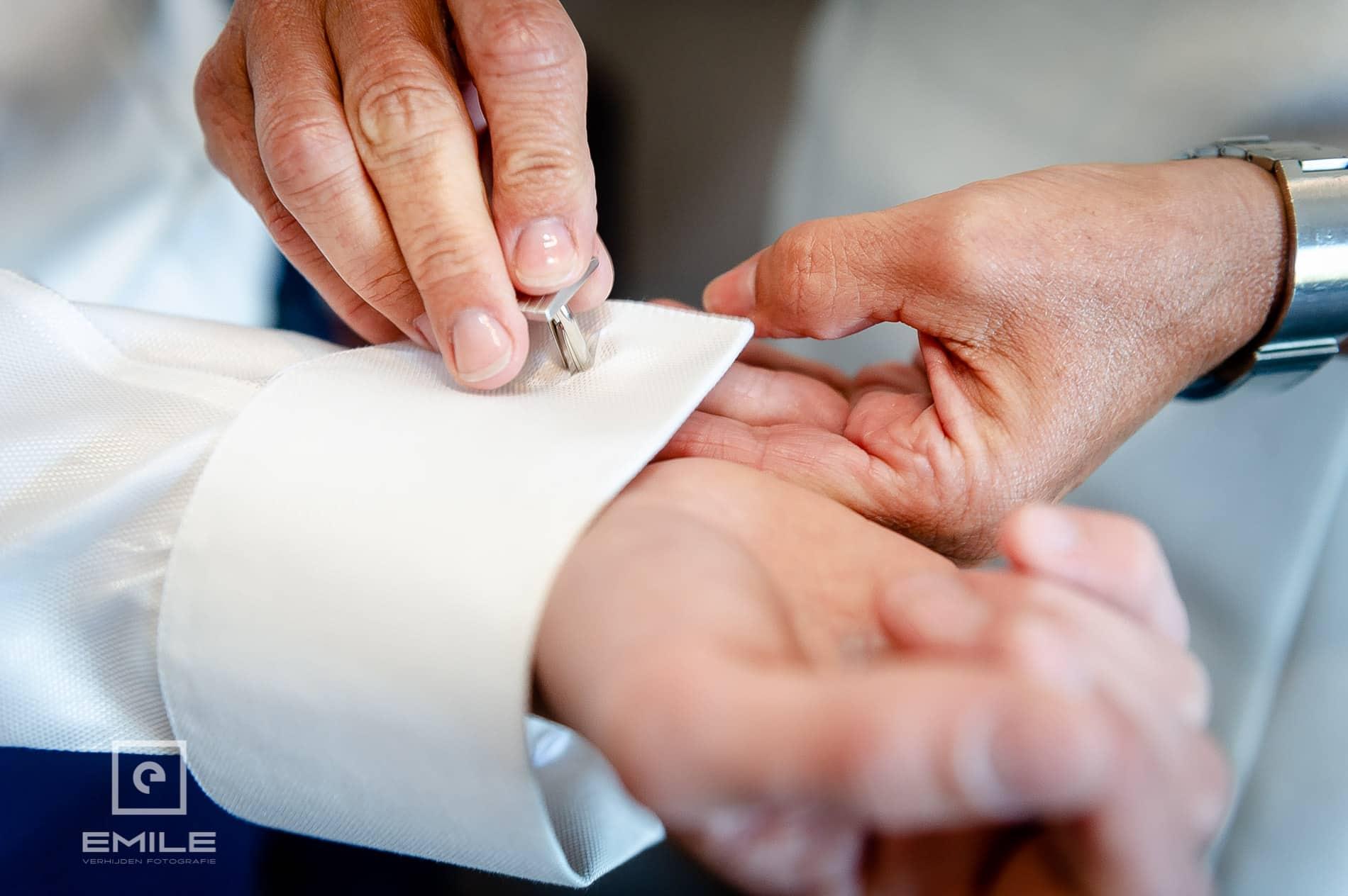 Manchet knopen van de bruidegom worden vastgemaakt. Bruidsfotograaf Venray