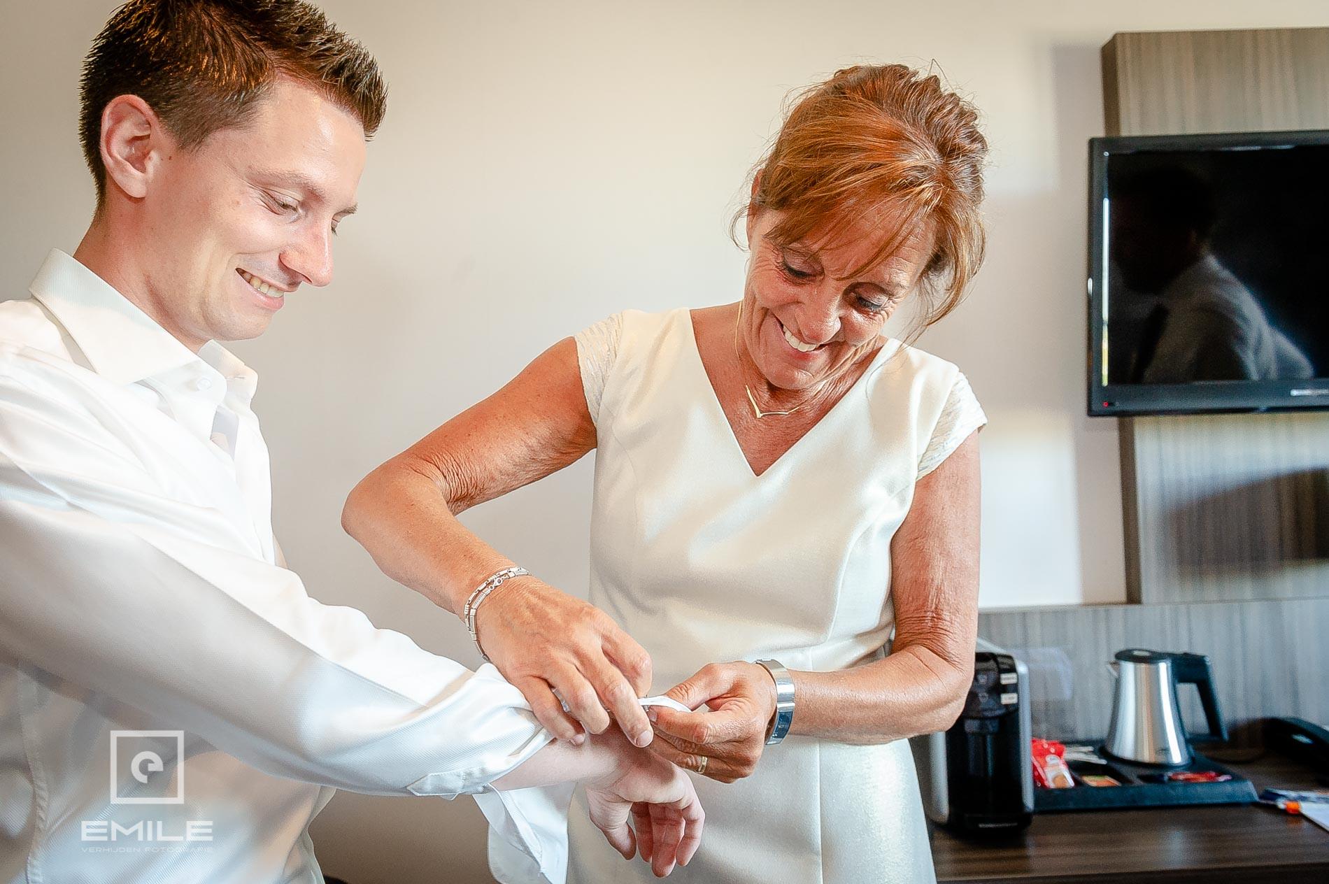 Moeder helpt bruidegom met de manchet knopen. bruidsfotograaf venray