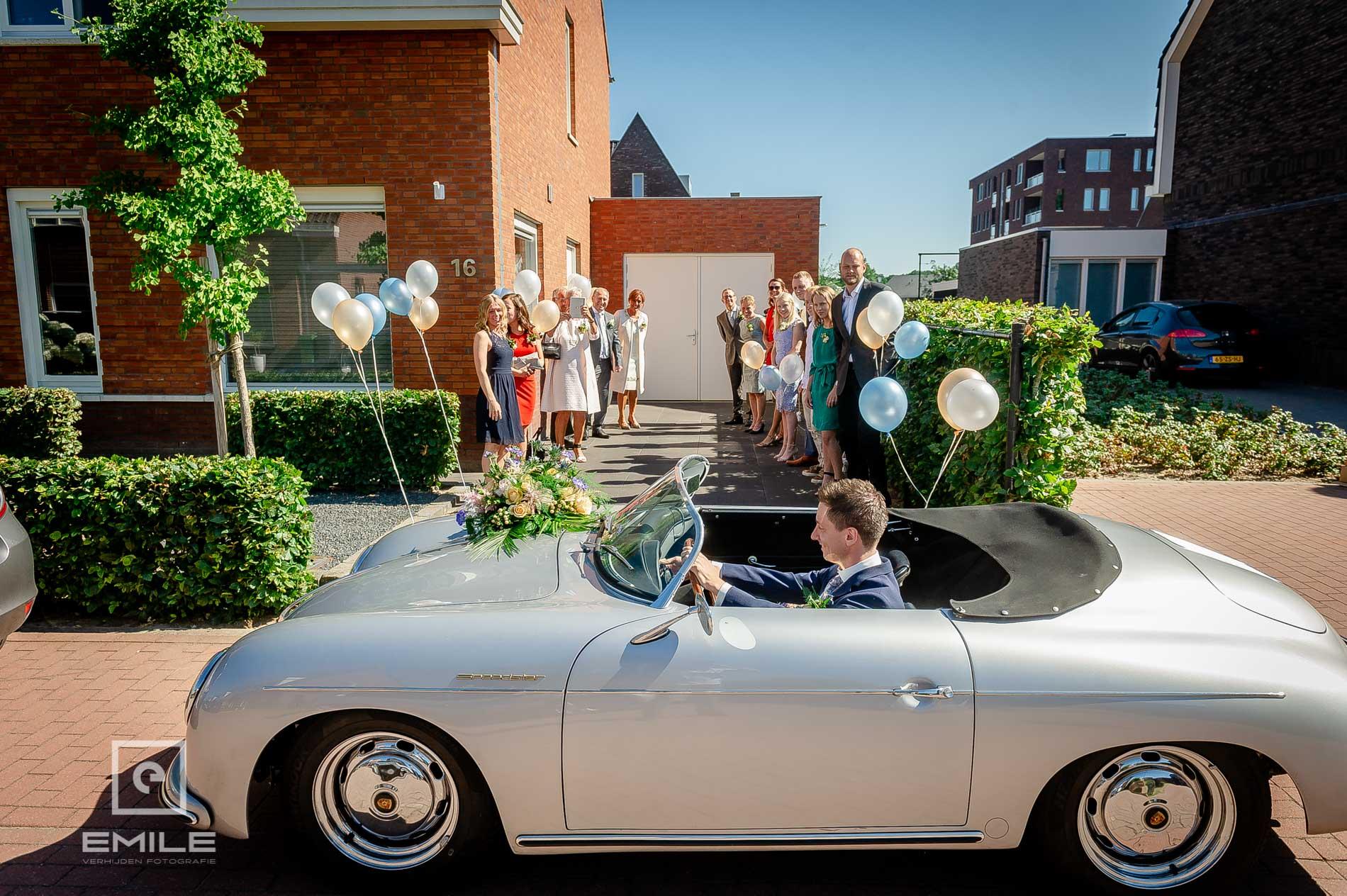 Bruidegom komt aan met de oude bruidsauto een Porsche