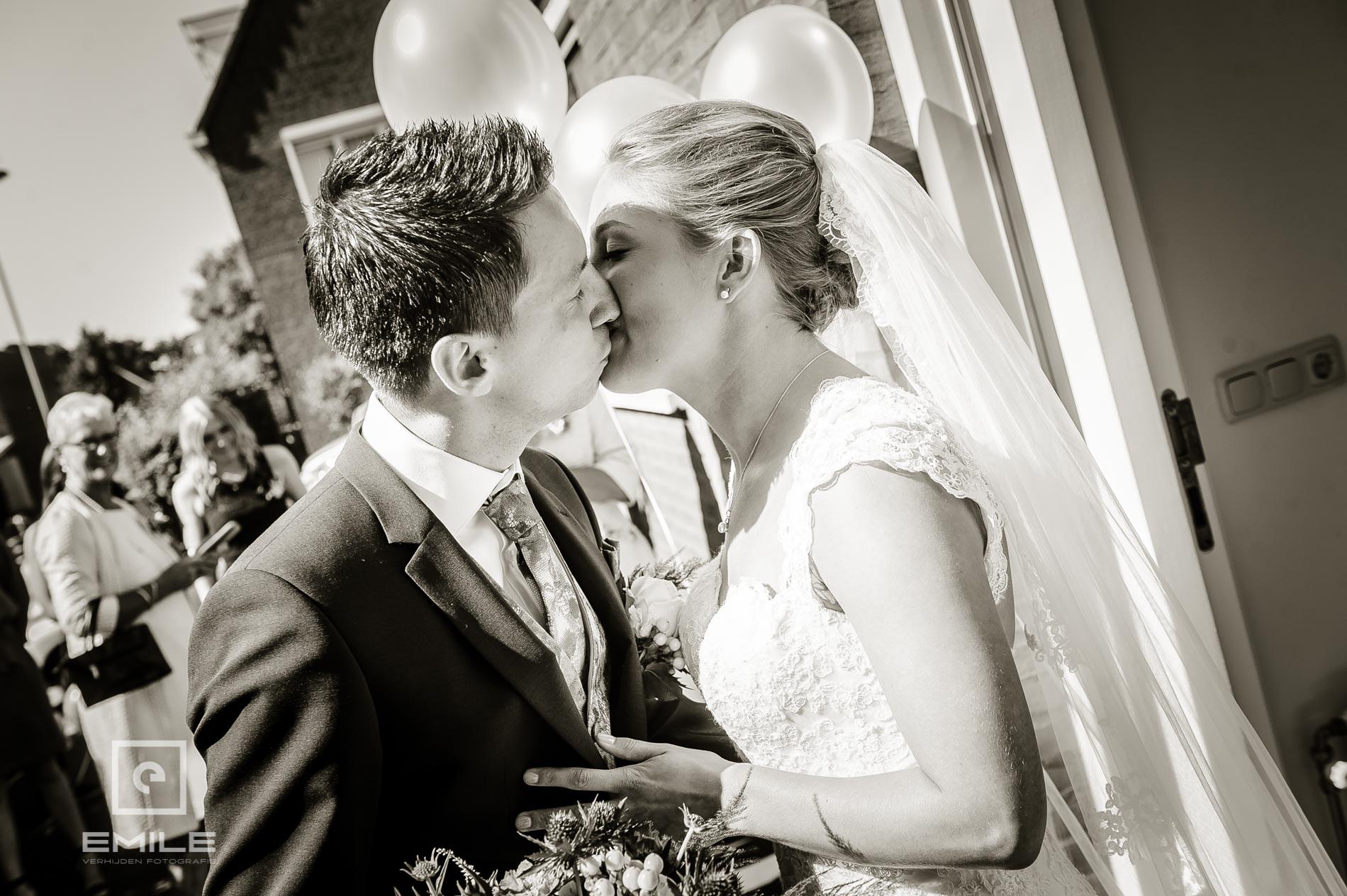 De eerste begroeting van het bruidspaar met een kus. bruidsfotograaf venray