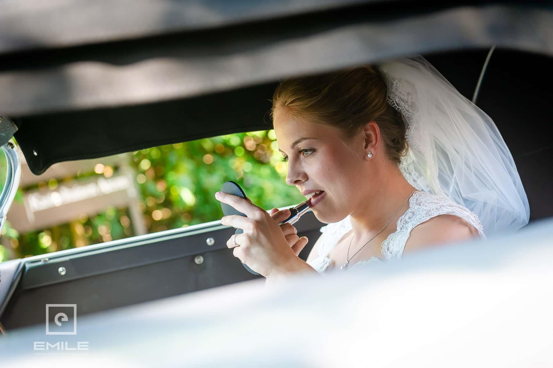 De bruid doet lippenstift op haar lippen. Bruidsfotograaf bij Kasteeltuinen Arcen