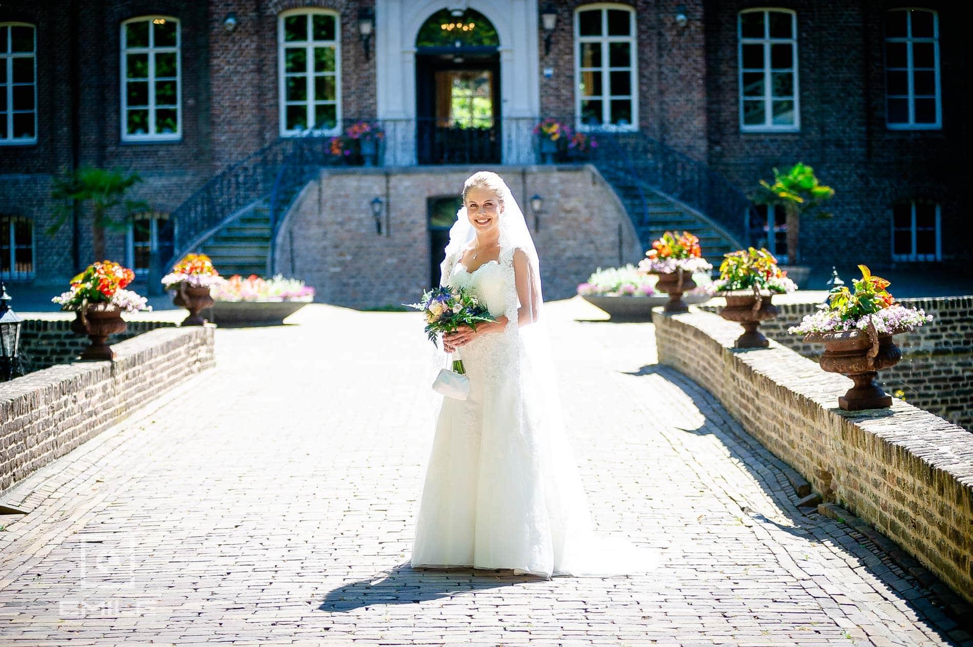 Bruidsfotograaf bij Kasteeltuinen Arcen, bruid staat voor het kasteel met boeket