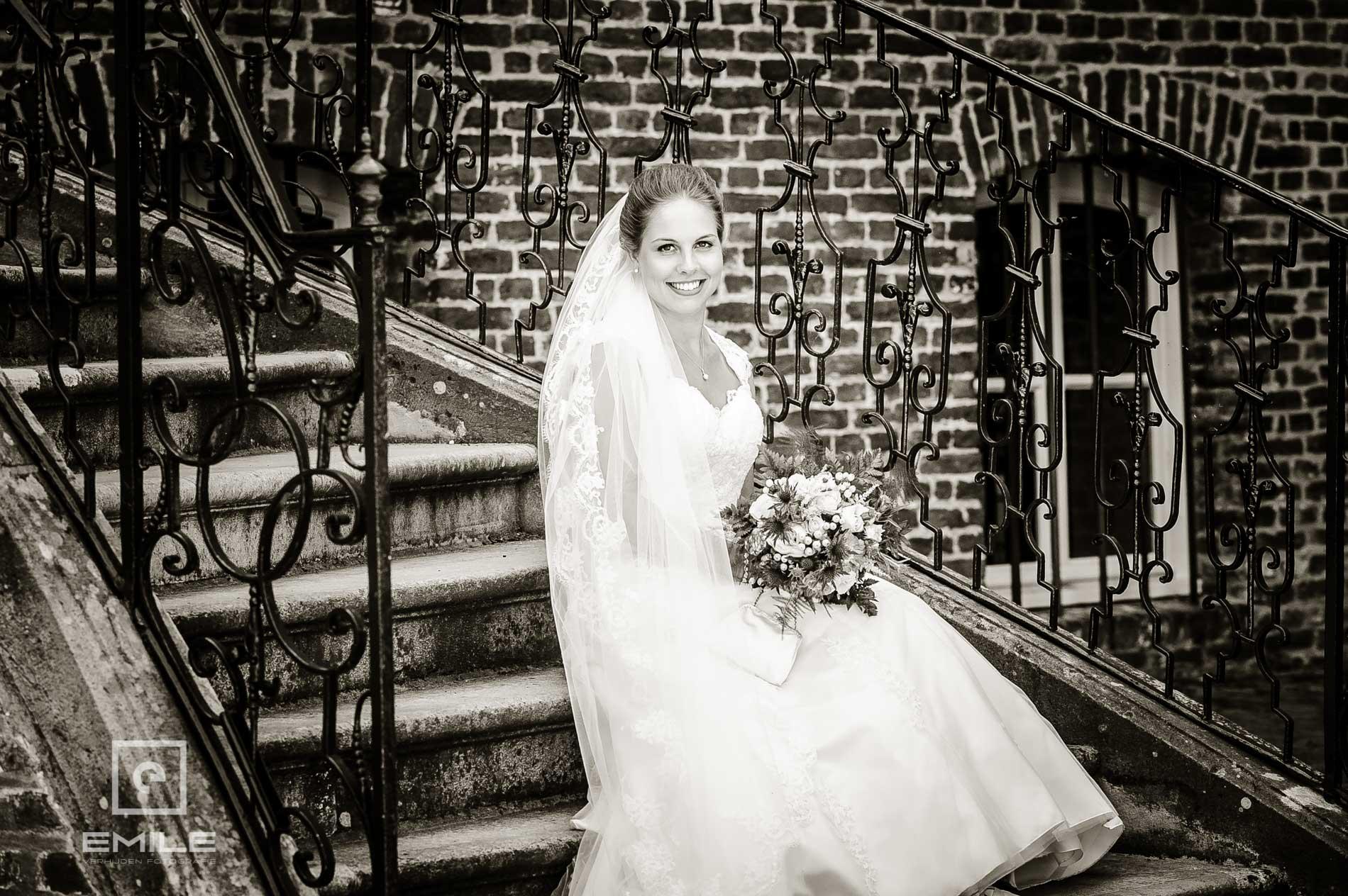 Bruidsfotograaf bij Kasteeltuinen Arcen. Bruid zit op trap van het kasteel