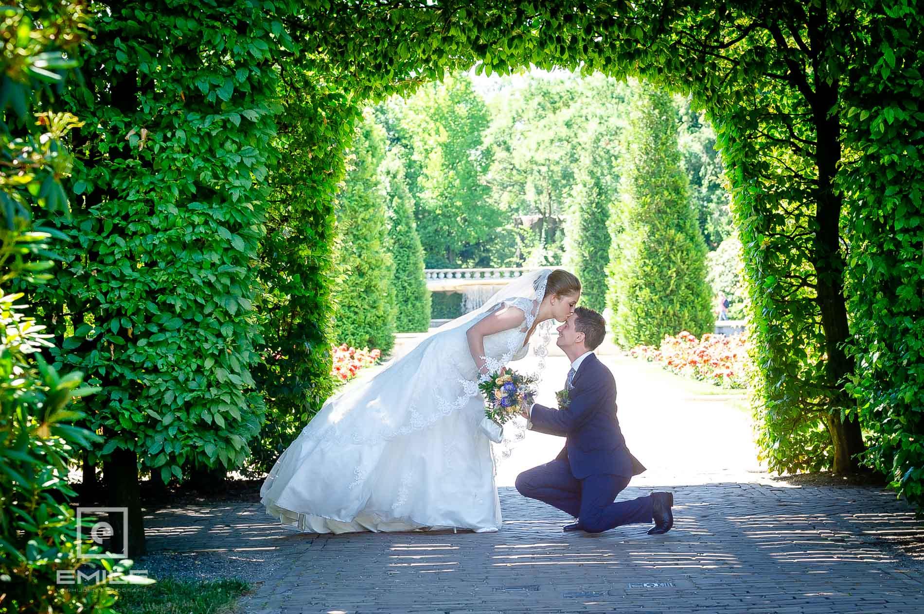 Bruidsfotograaf met bruidspaar in  Kasteeltuinen Arcen. Bruidspaar geeft elkaar een kus