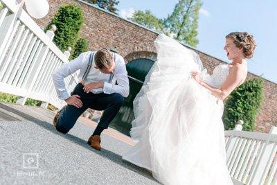 Bruidegom kijkt bruid onder de rok. Bruidsfotograaf Heerlen