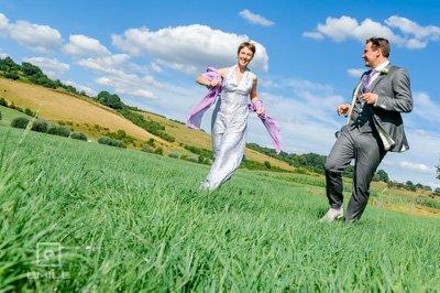 Bruidspaar rent door de wei bij Viva Lanterne. Bruidsfotograaf Maastricht