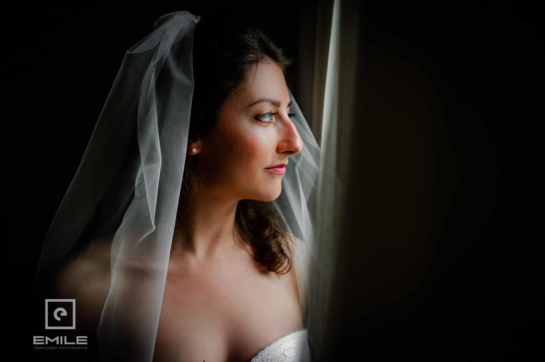 Prachtige bruid staat voor het raam. Bruidsfotograaf Chateau Presseux Belgie