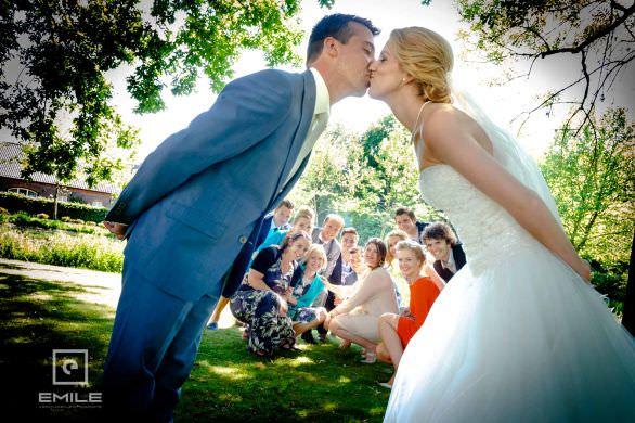 Bruidspaar kust elkaar in een boog samen met hun vrienden