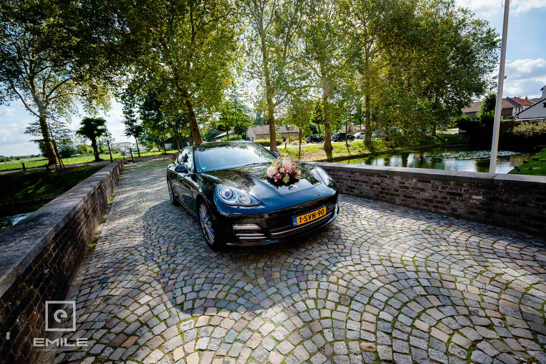 Bruidsfotograaf Kasteel Limbricht bruidsauto komt aangereden over de brug  van het kasteel