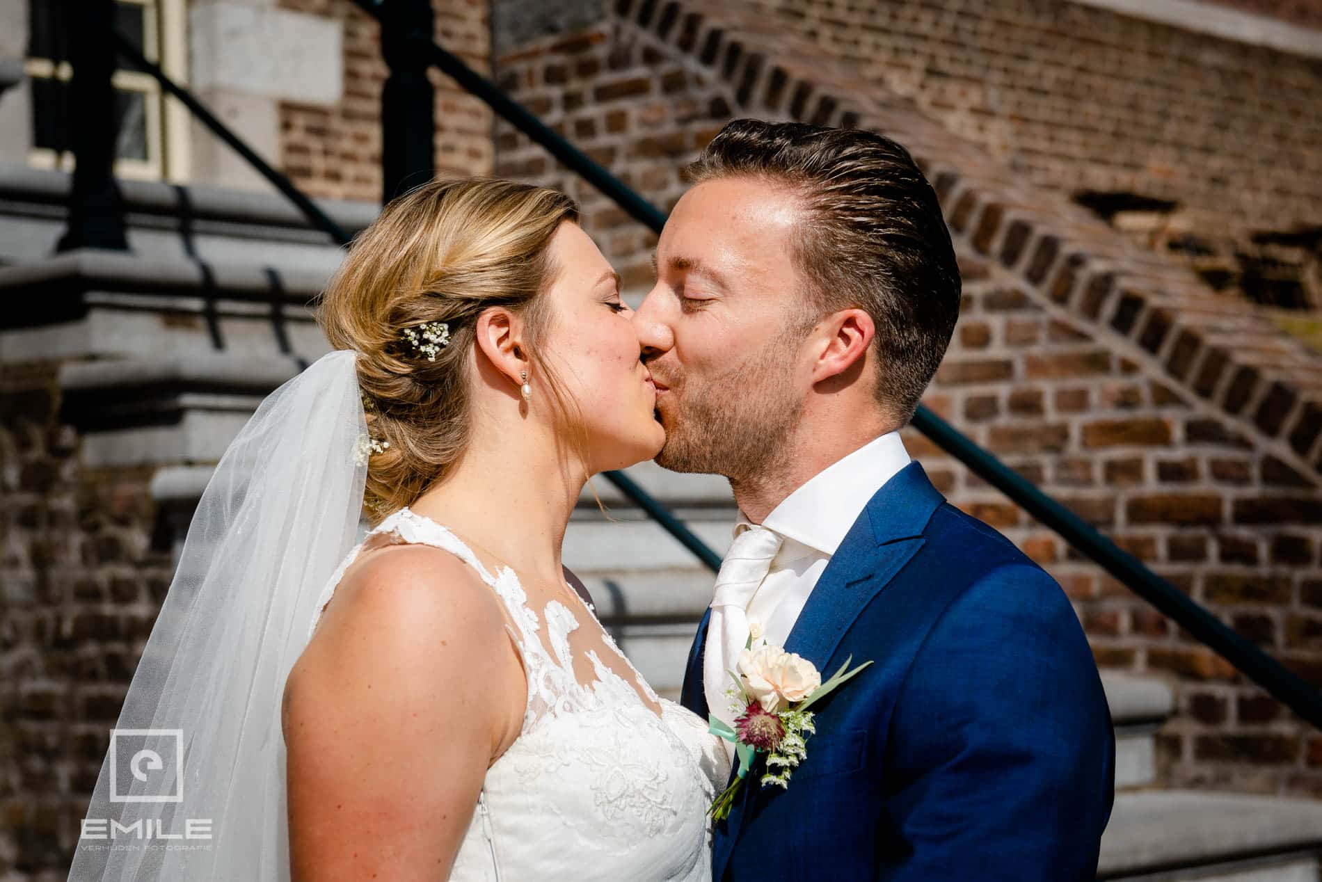 De bruidskus, het bruidspaar kust elkaar. Trouwen in Limburg