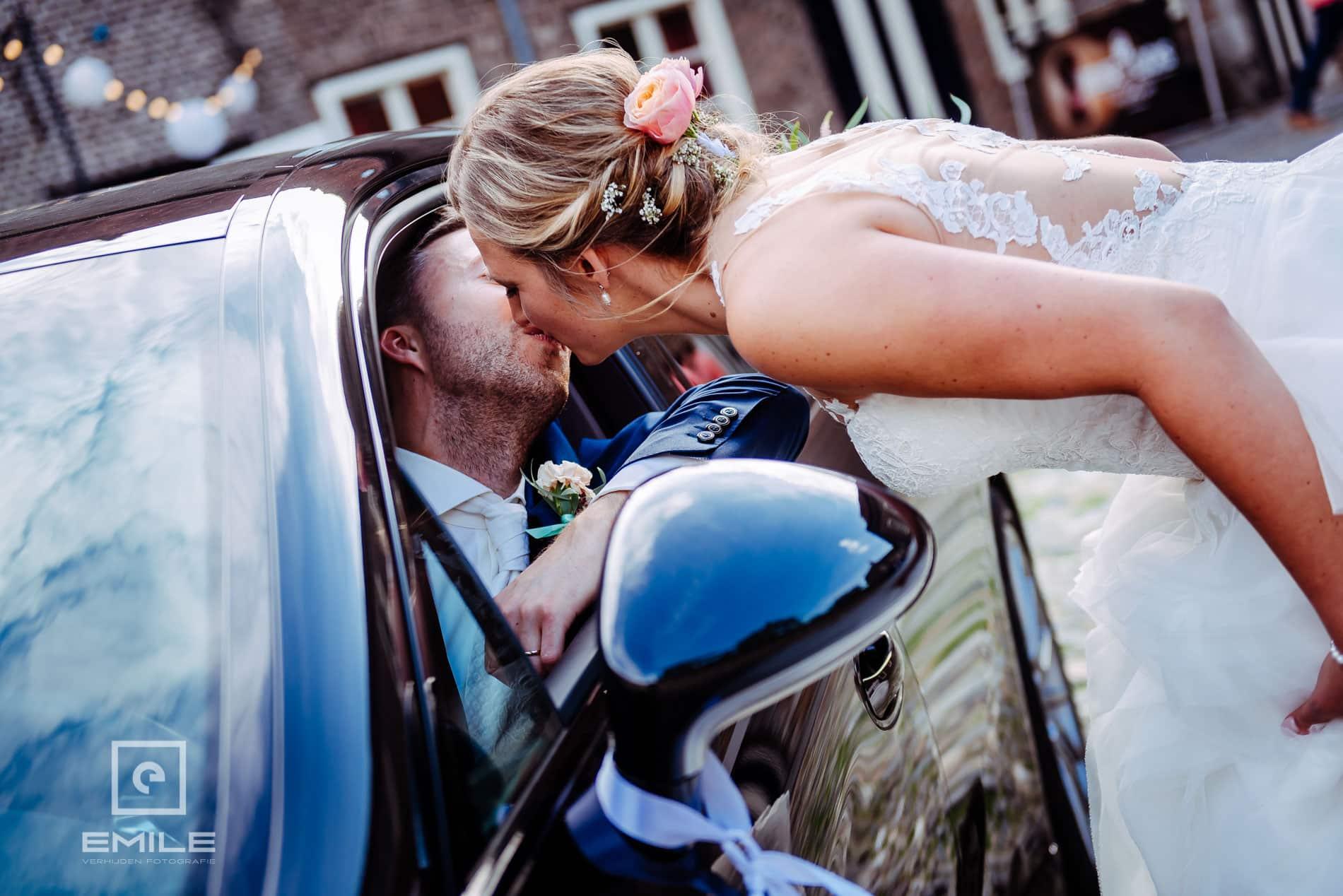 Huwelijksfotograaf Kasteel Limbricht -  kus bij bruidsauto