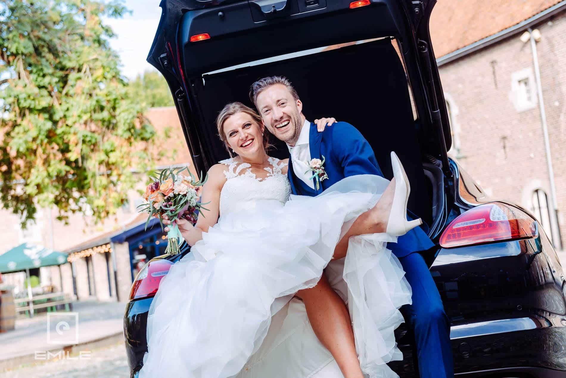 Bruidsfotograaf Kasteel Limbricht - bruidspaar samen in kofferbak van bruidsauto. Top foto!