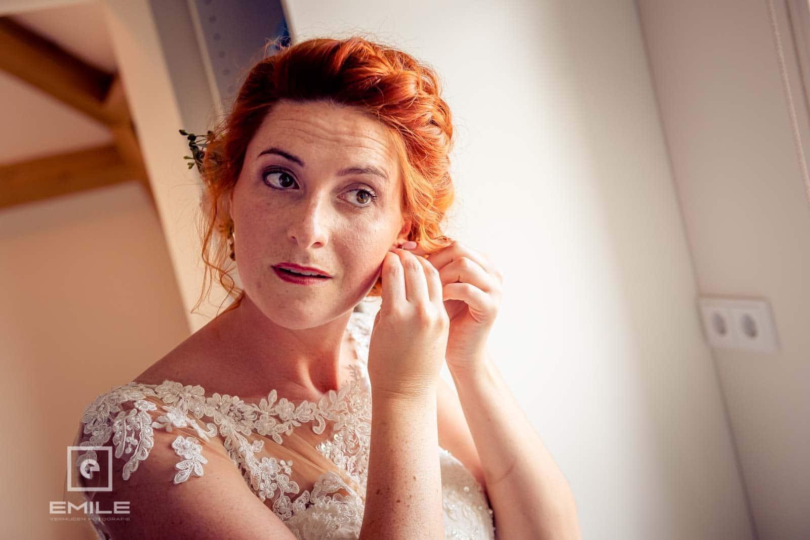De oorbellen worden ingedaan door de bruid zelf. Bruiloft Wylre Zuid-Limburg