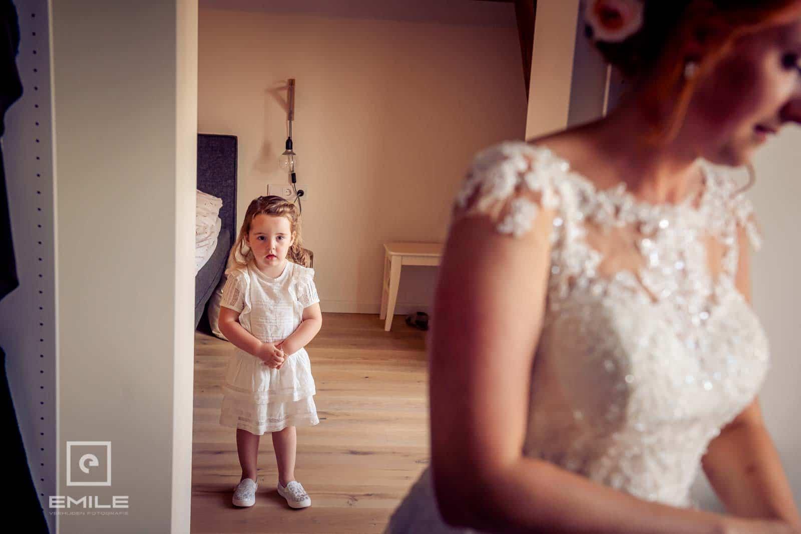 De kleine meid is erg nieuwsgierig wat de bruid aan het doen is . Bruiloft Wylre Zuid-Limburg