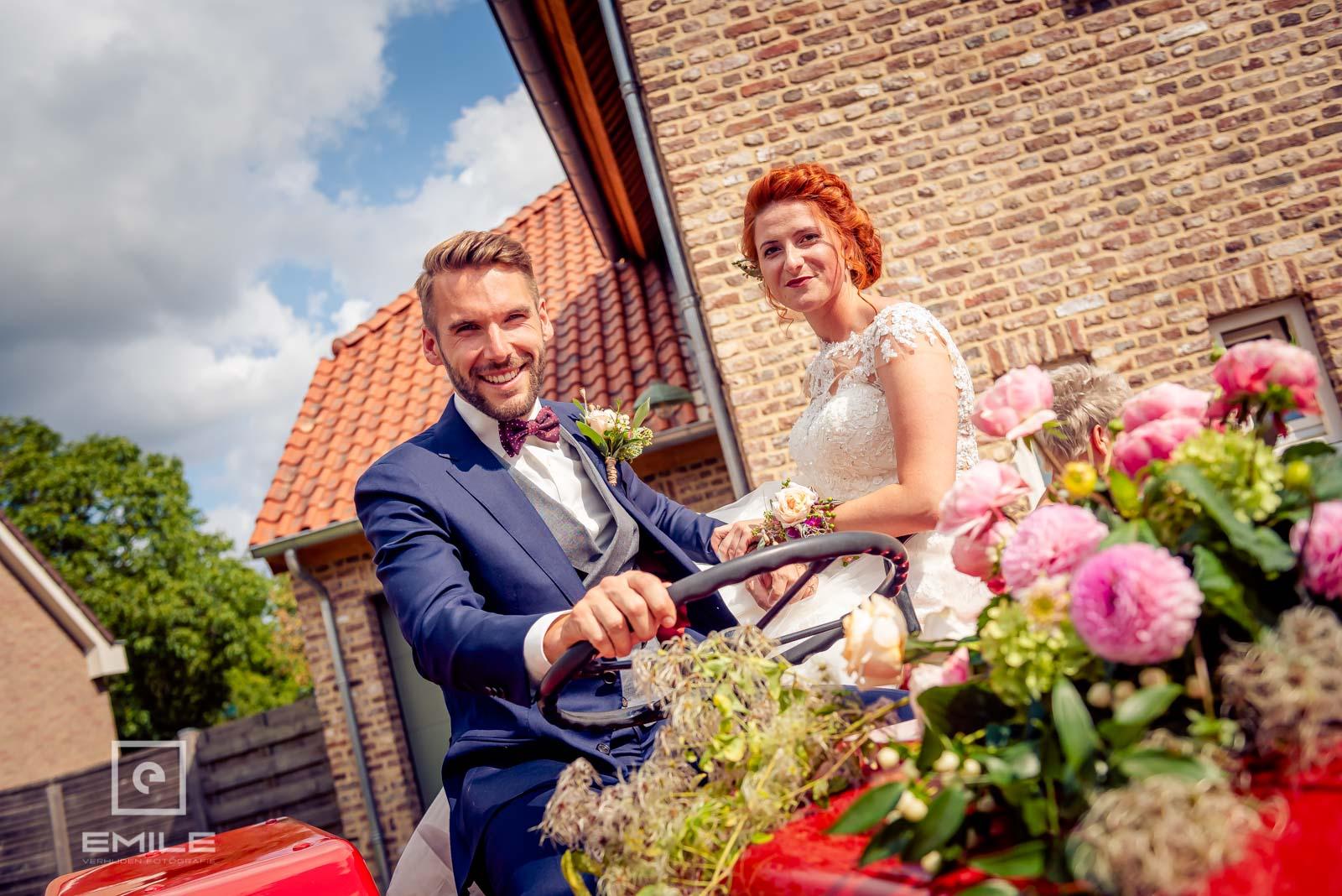 Bruid en bruidegom samen op de tractor en gaan op weg naar de kerk van Wylre