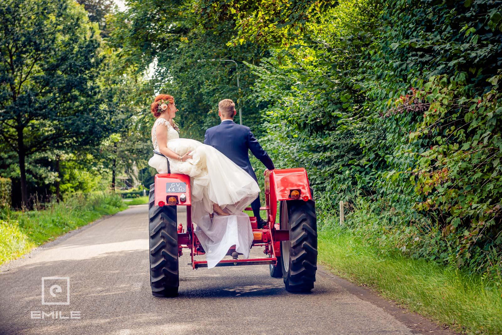 Met de tractor rijdend gaat het bruidspaar naar de kerk